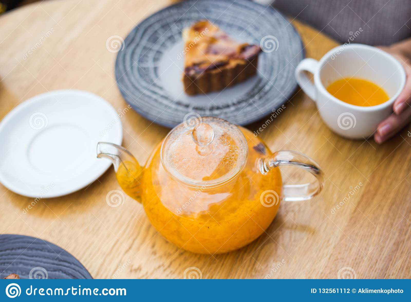 Teapot of orange tea and a pice of cake