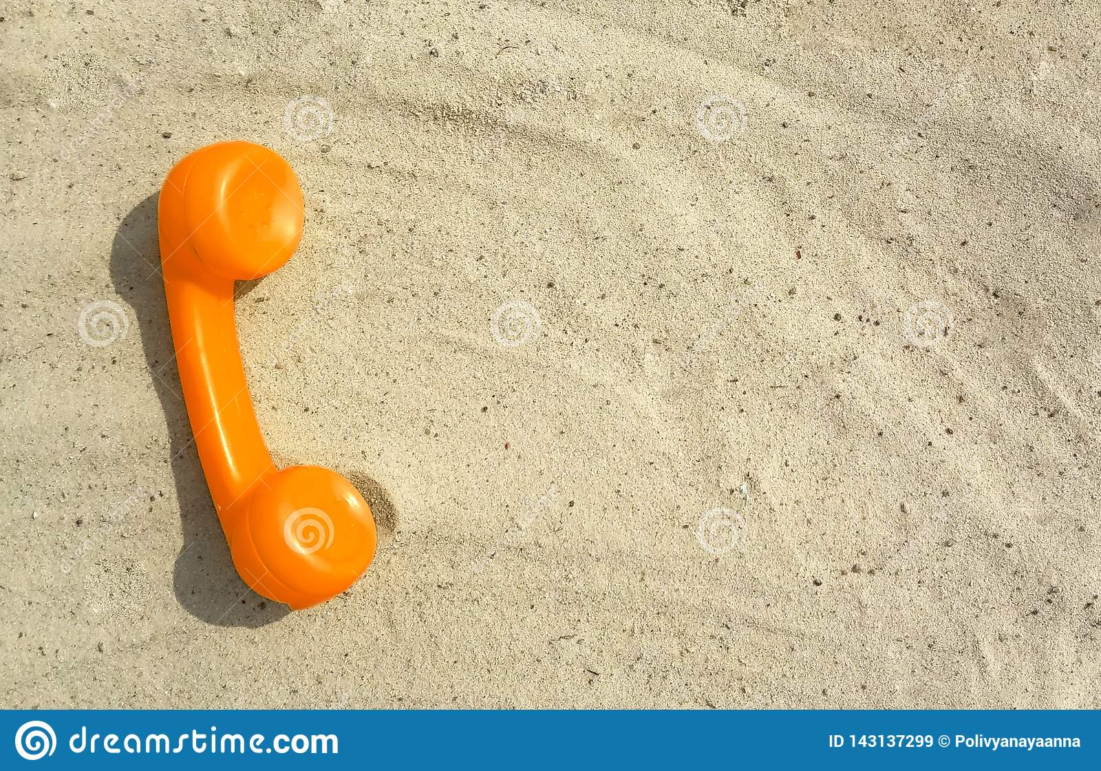 Orange tube of an old vintage phone is lying on the sand