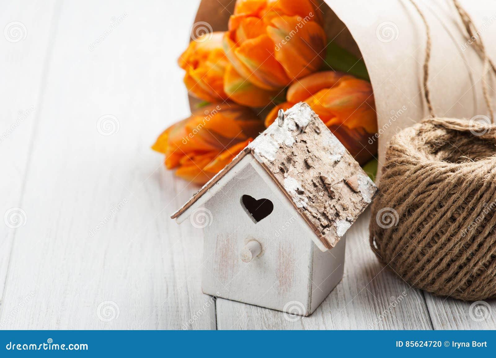 Orange tulips, wooden heart shape bird house and twine