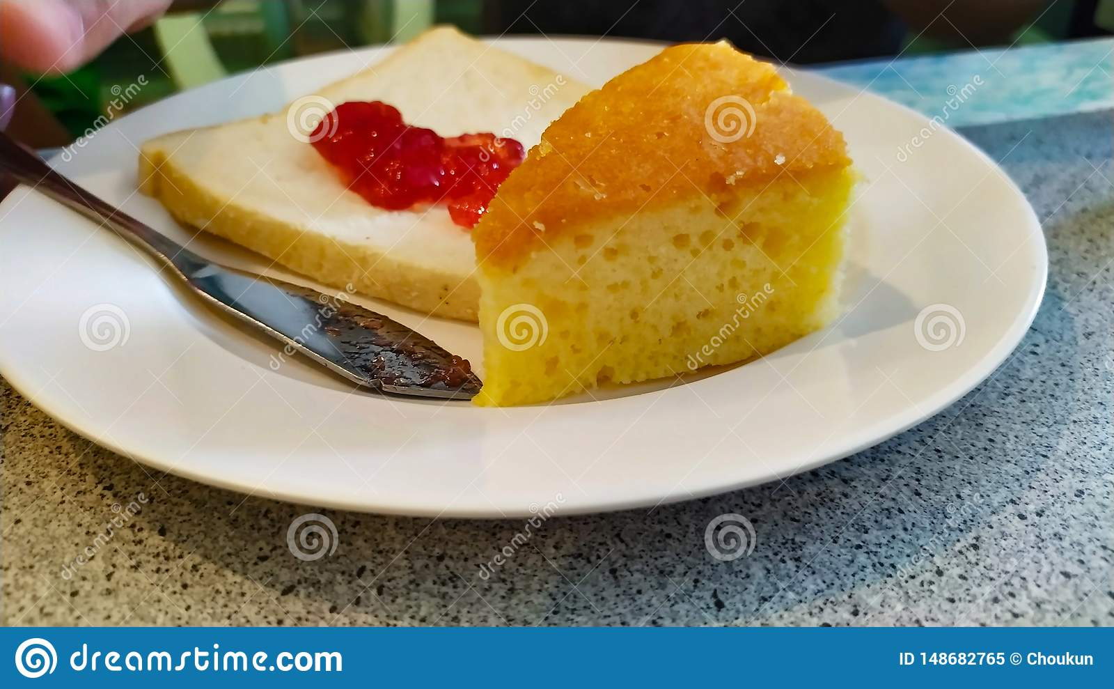Cake and strawberry jam on bread on dish white very delicious