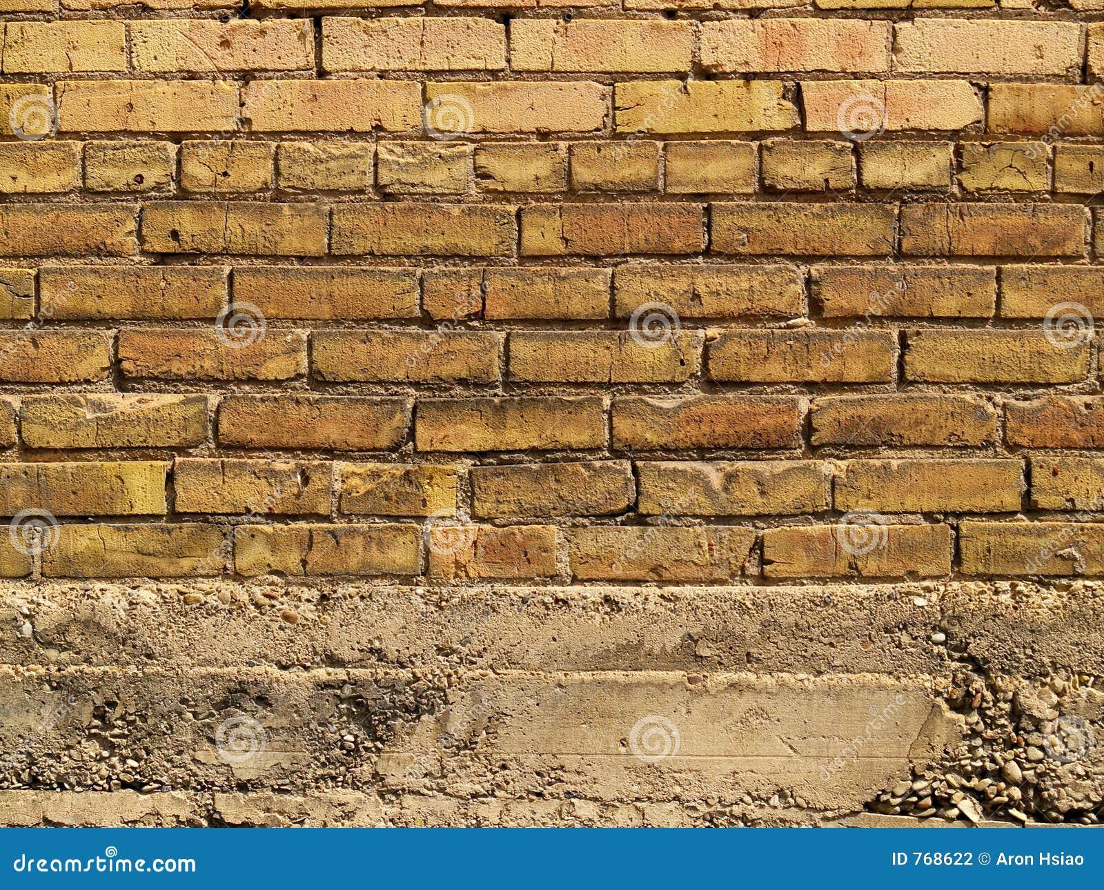 Orange and yellow brick wall over concrete