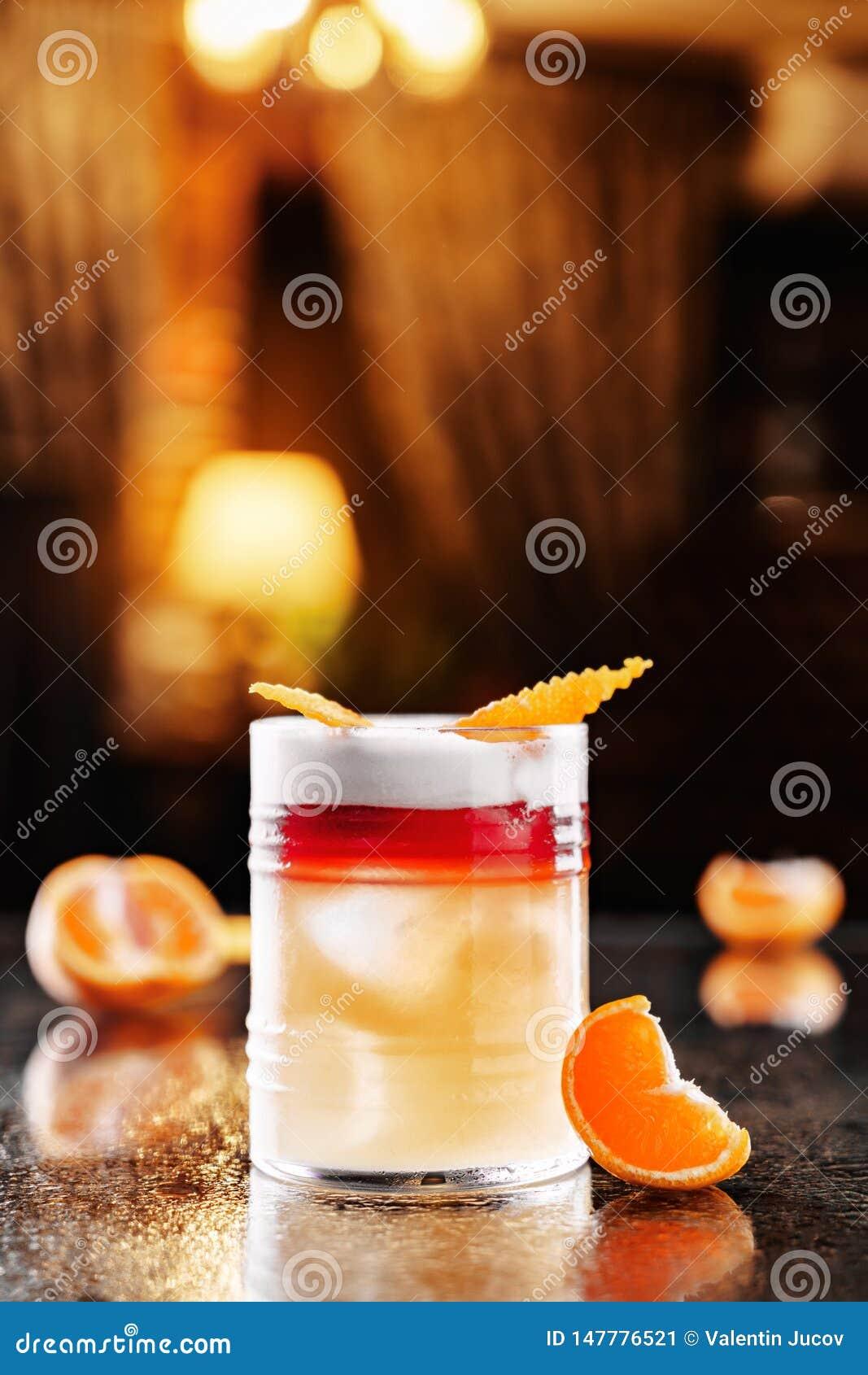 Orangeade fraîche avec la vodka, les mandarines et la glace en verre sur le contexte de l atmosphère de restaurant Boissons et co