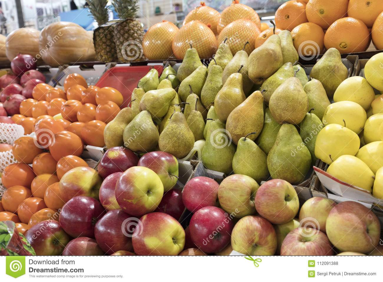 Oranges, apples, pears, pineapple, pomegranate, pumpkin, persimmonlie on the market counter for sale