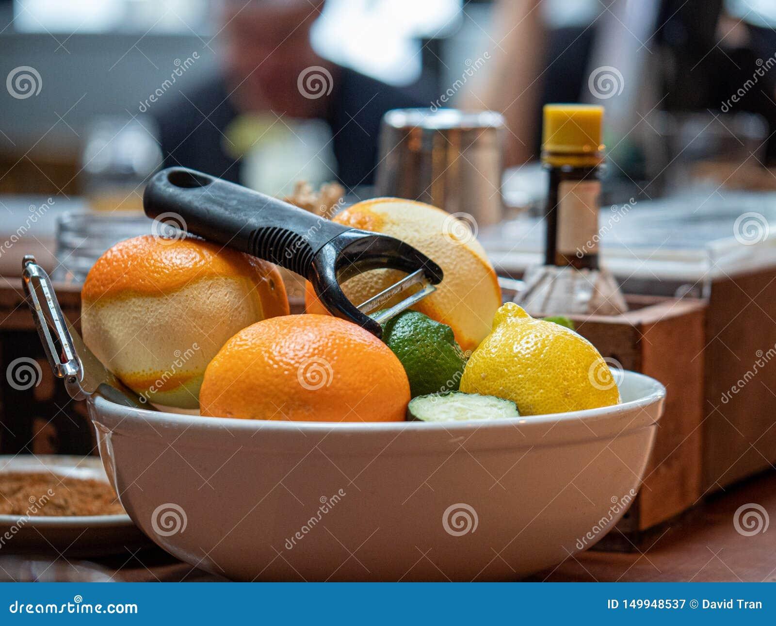 Oranges, chaux, et citrons pour éplucher la séance dans une cuvette sur la barre pour créer des boissons