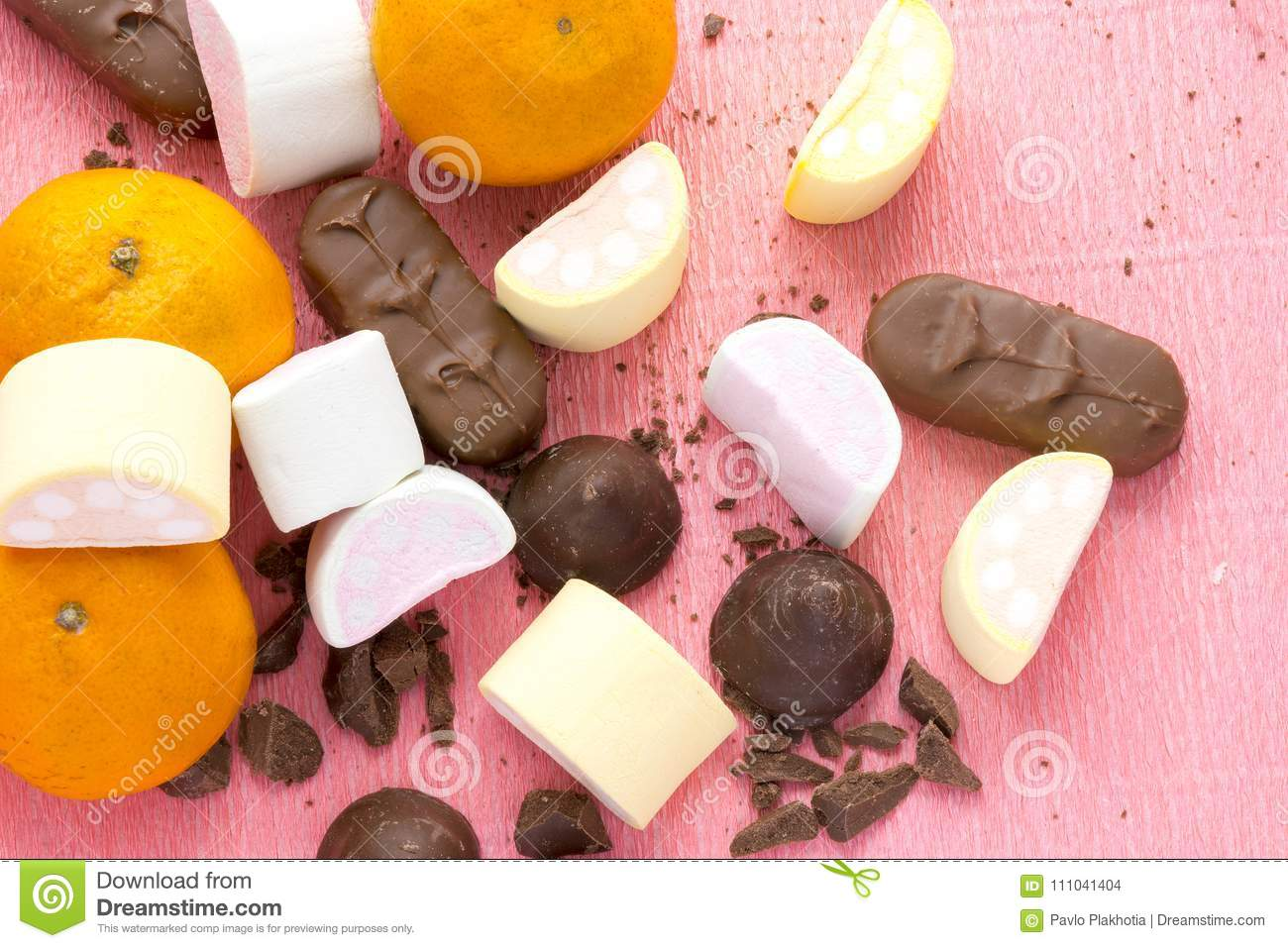 Oranges, chocolate and zephyr on pink background. Cooking of homemade sweets.