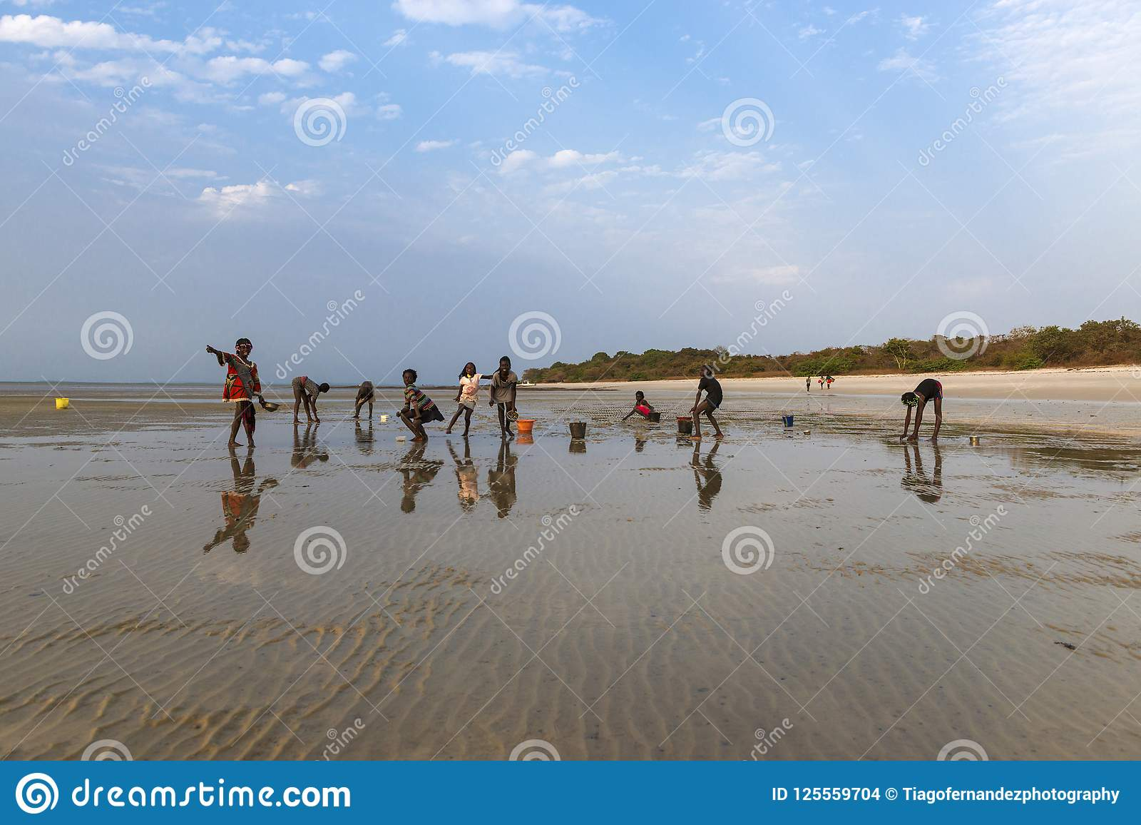 Group of children collecting cockles and playing at the beach in the island of Orango at sunset.