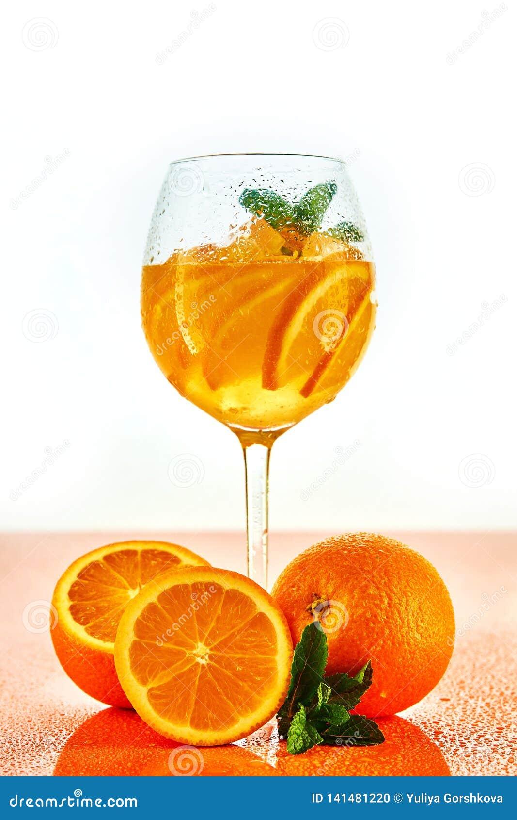 Oranje cocktail in wijnglas met munt op witte achtergrond met sinaasappelen