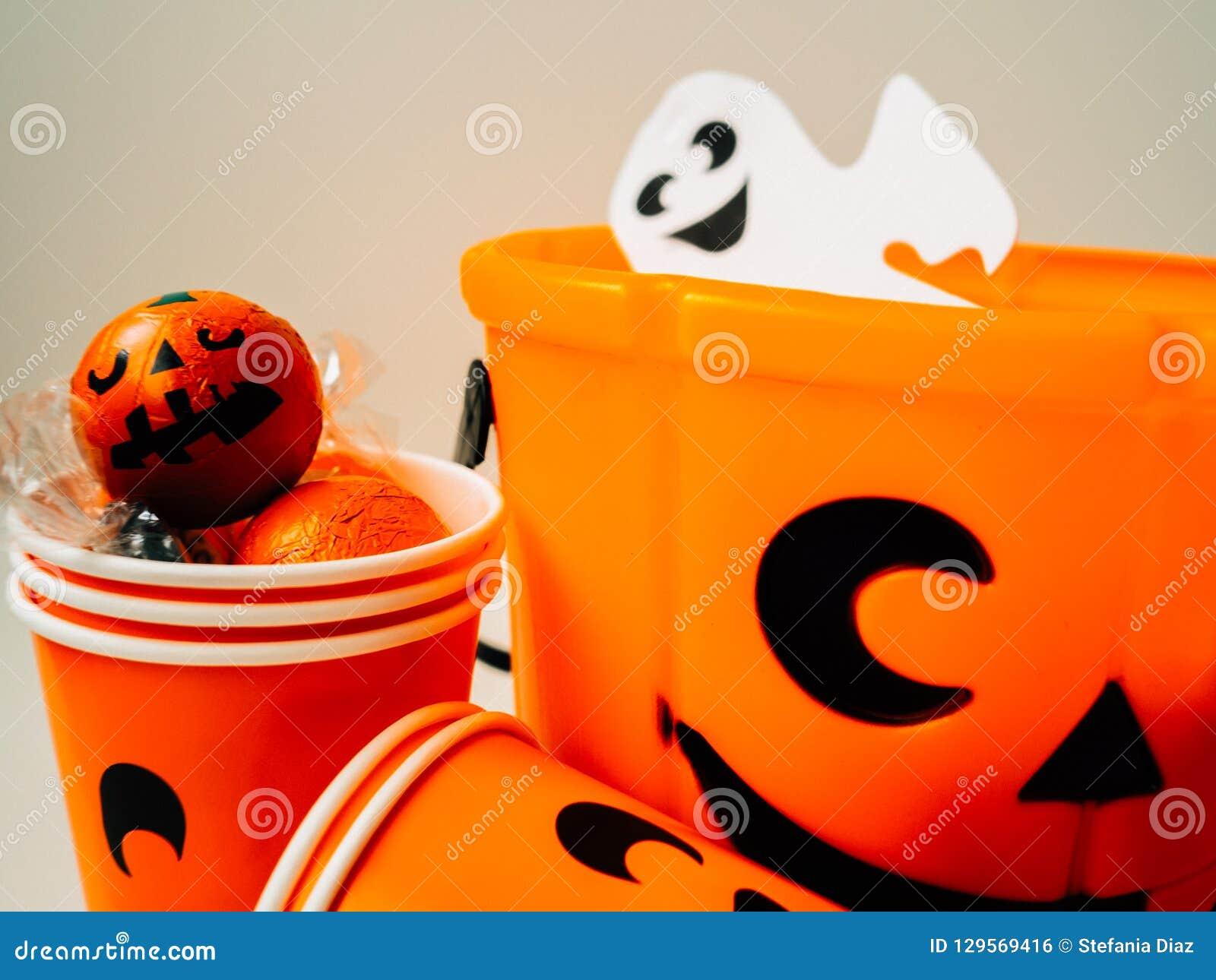 Oranje die pompoen met chocolade wordt gevuld en een oranje kartonkop met gelukkig gezicht en een wit spook
