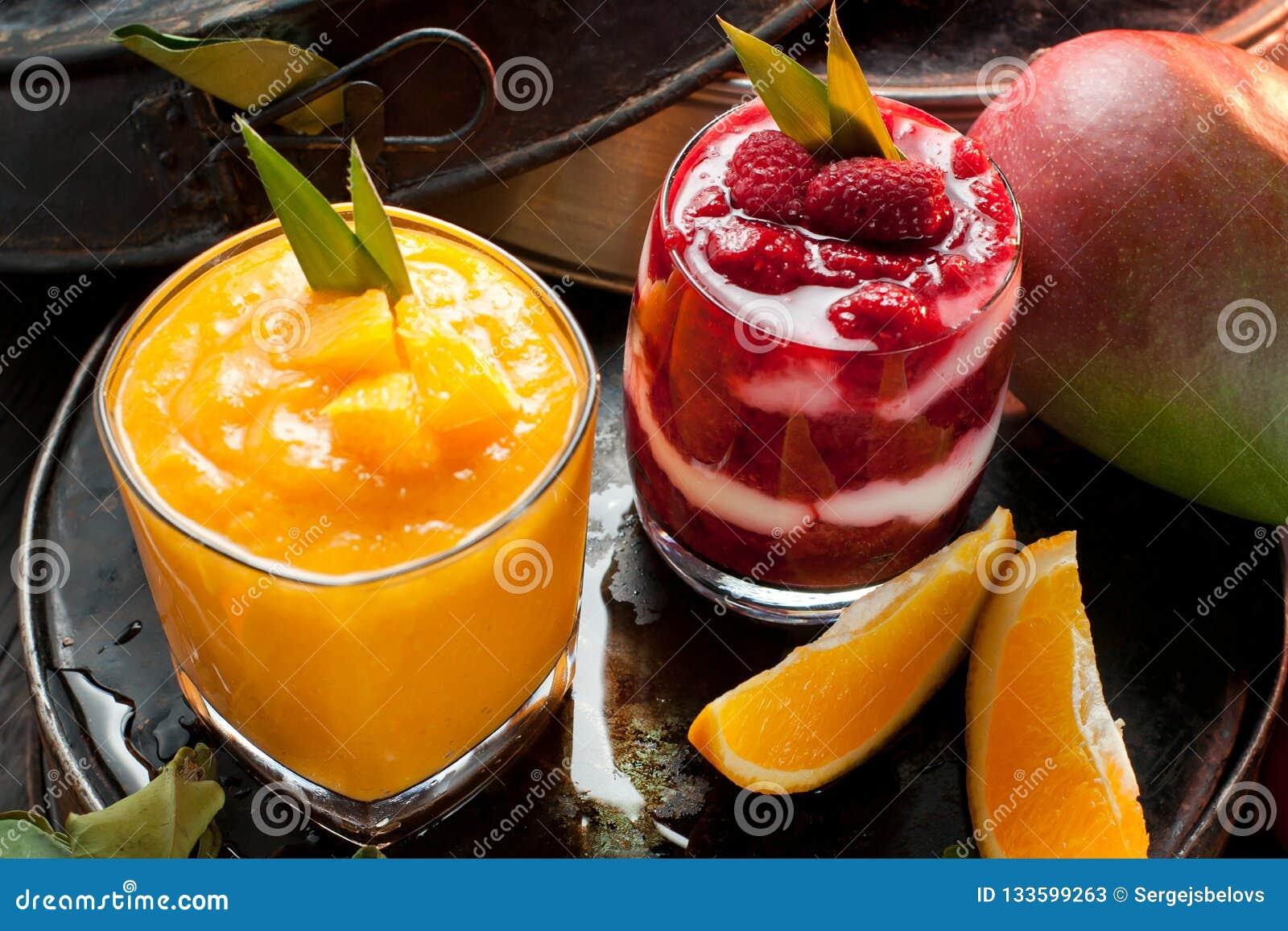 Oranje en Rode smoothie en oranje vruchten met groene bladeren op D