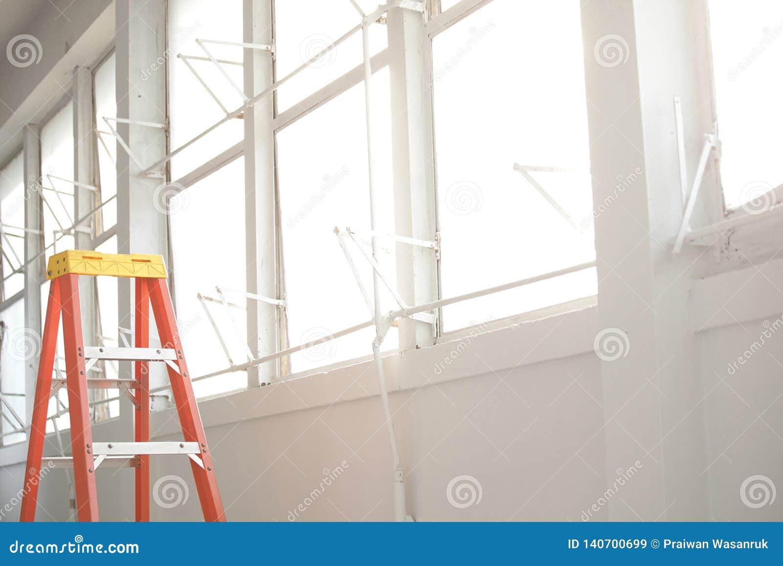 Oranje ladder op witte venstergang