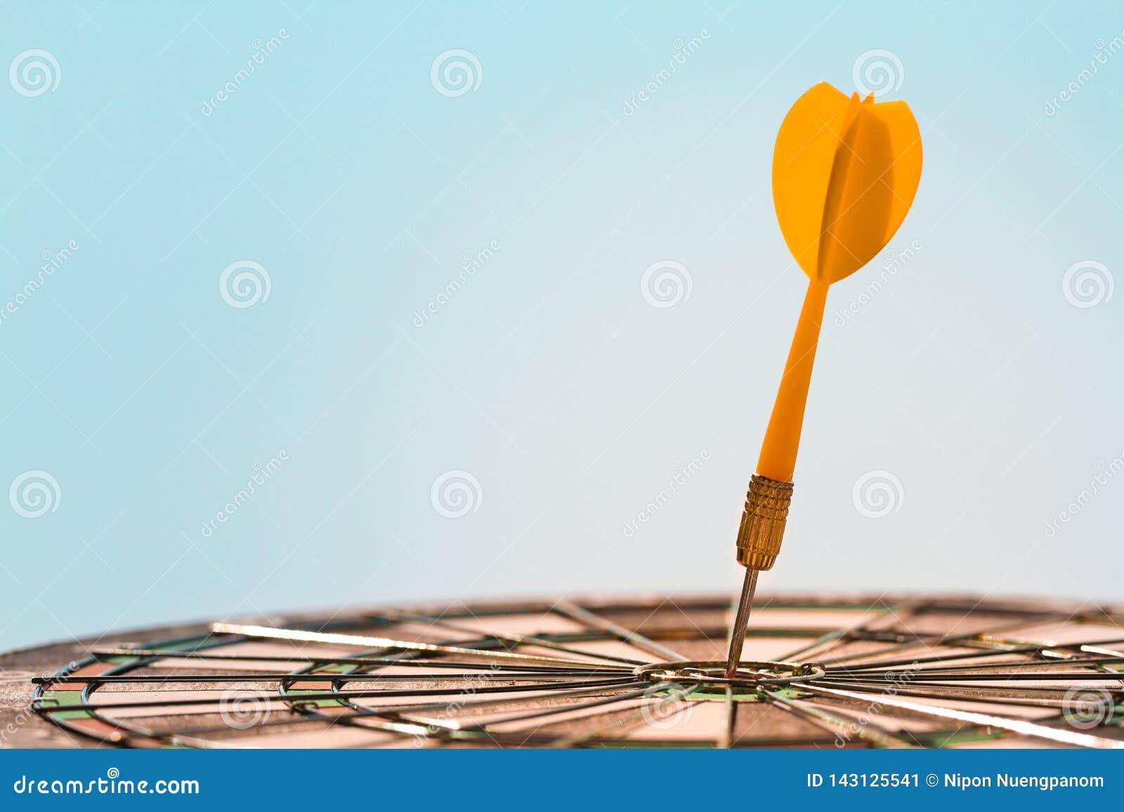 Oranje pijltjepijl die stier-oog in centrum van dartboard op blauwe hemelachtergrond raken