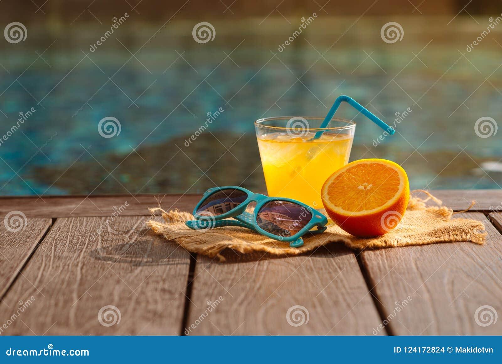 Oranje verse sap smoothie drank, zonnebril dichtbij zwembad