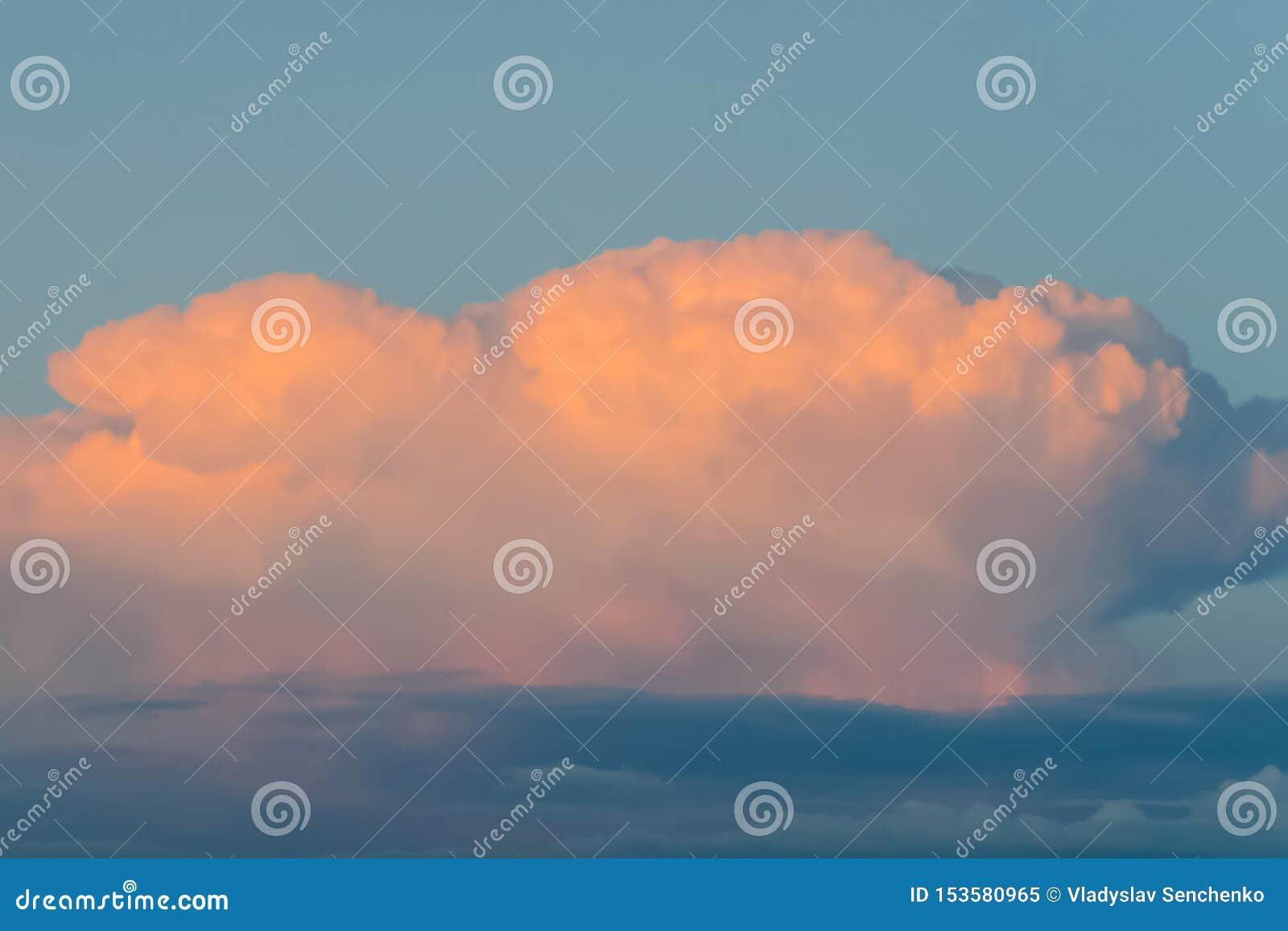 Oranje wolk op blauwe hemel bij zonsondergang