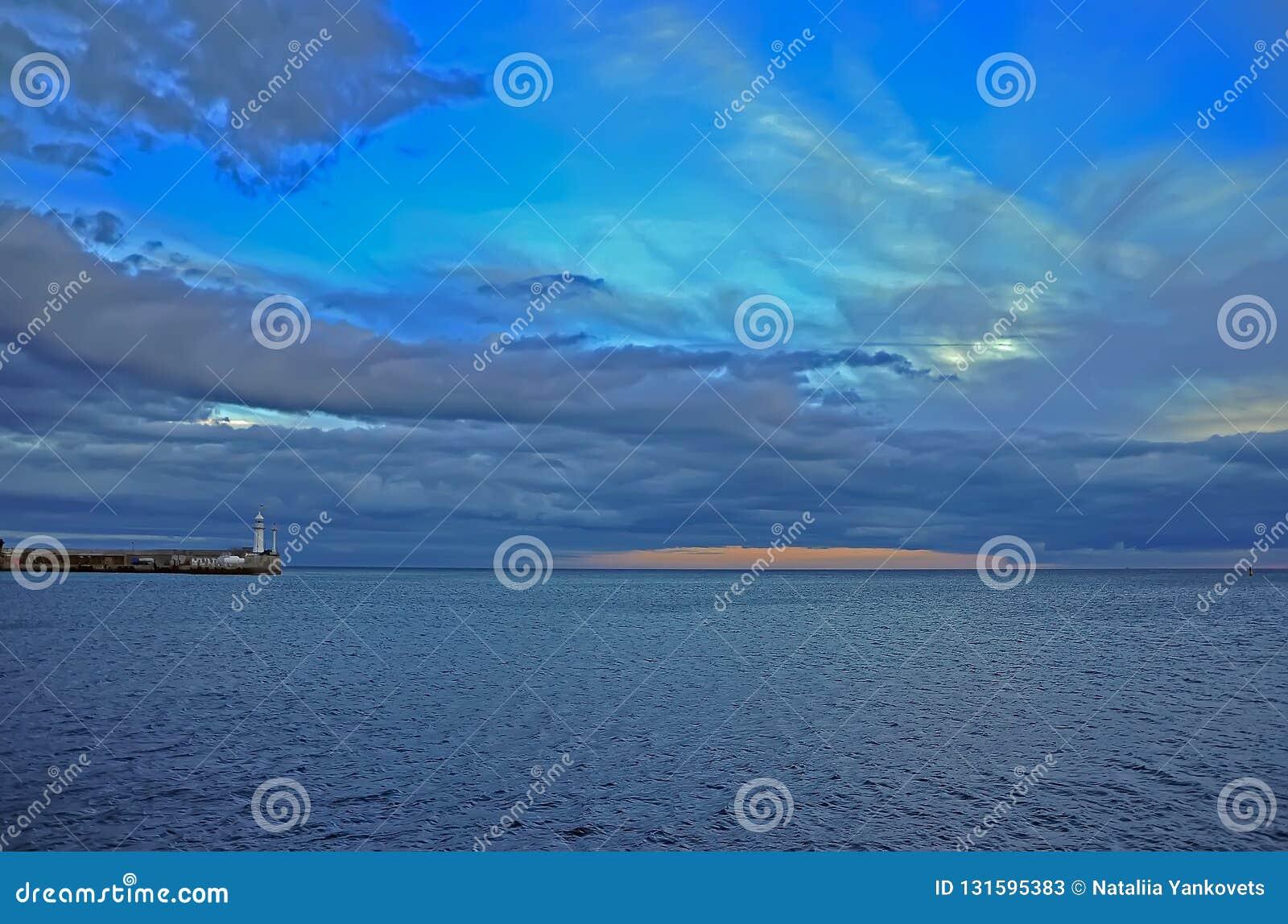 Oranje zonsondergang amid blauw-Blauwe de herfsthemel over het overzees dichtbij de vuurtoren in de Krim