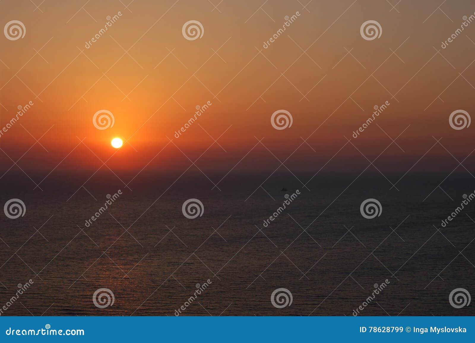 Oranje zonsondergang boven het kalme overzees