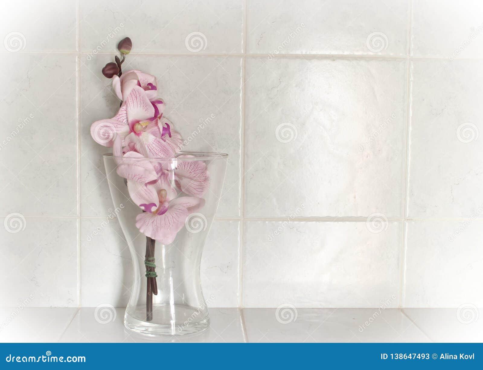 Orchidee di plastica nel vetro con i precedenti bianchi