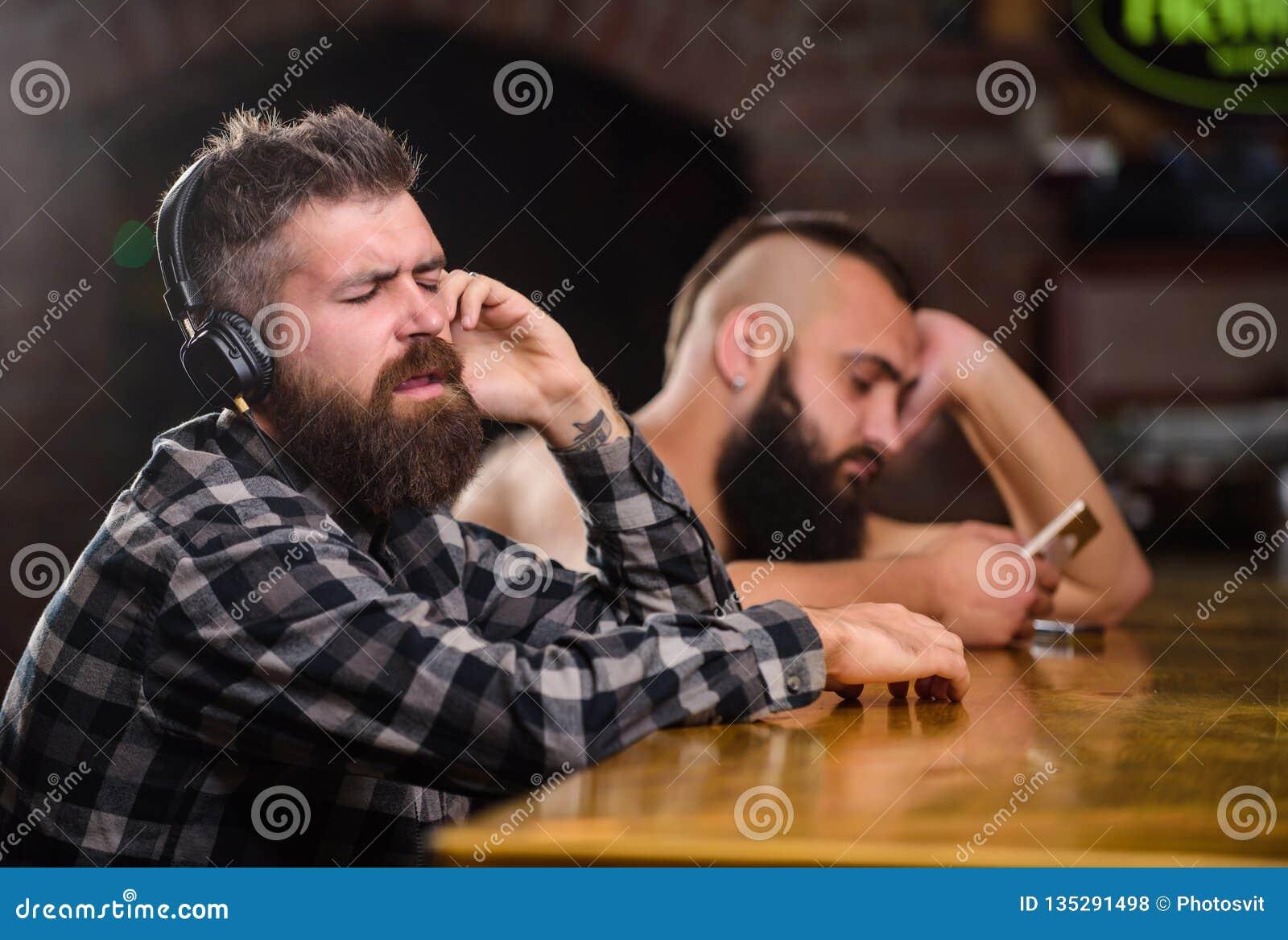 Ordedranken bij barteller Mensen met hoofdtelefoons en smartphone het ontspannen bij bar Vermijd mededeling Vluchtwerkelijkheid
