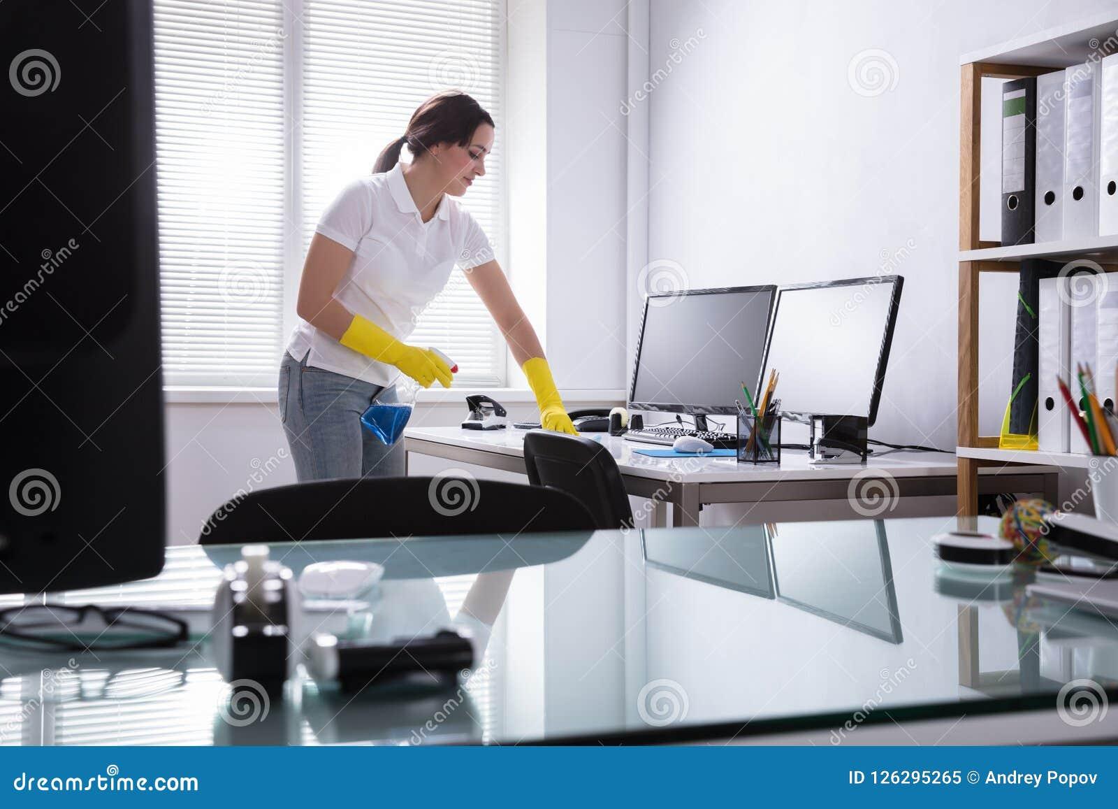 Ordenador de la limpieza de la mujer en oficina