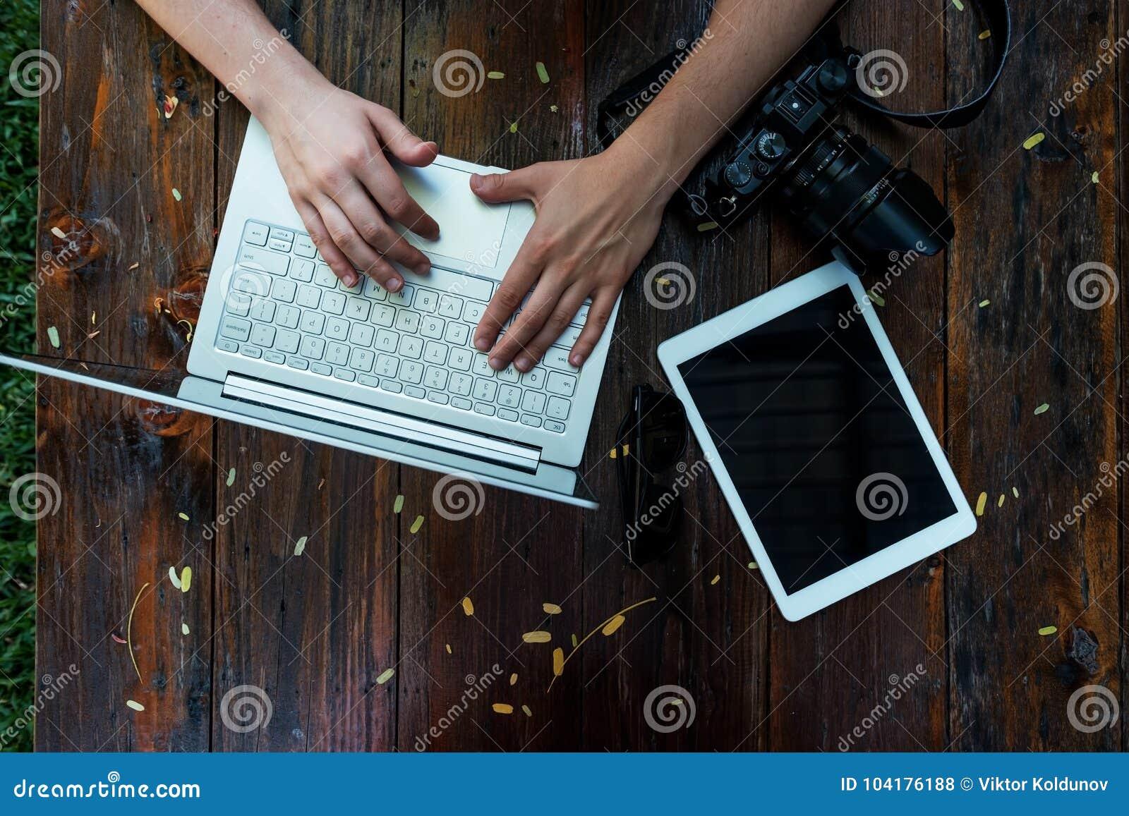 Ordenador portátil, cámara en fondo de madera Endecha plana del lugar de trabajo del freelancer o del empresario individual