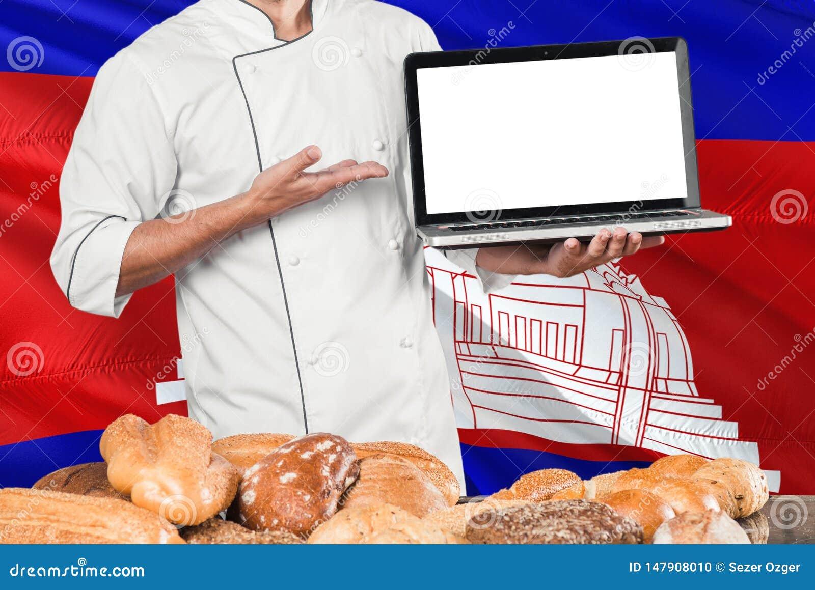 Ordenador portátil camboyano de la tenencia del panadero en la bandera de Camboya y el fondo de los panes Uniforme que lleva del