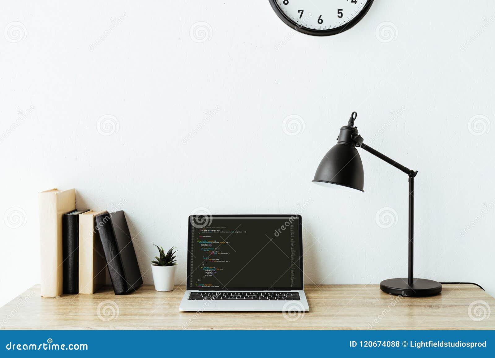Ordenador portátil con código de programa y libros en el escritorio del trabajo