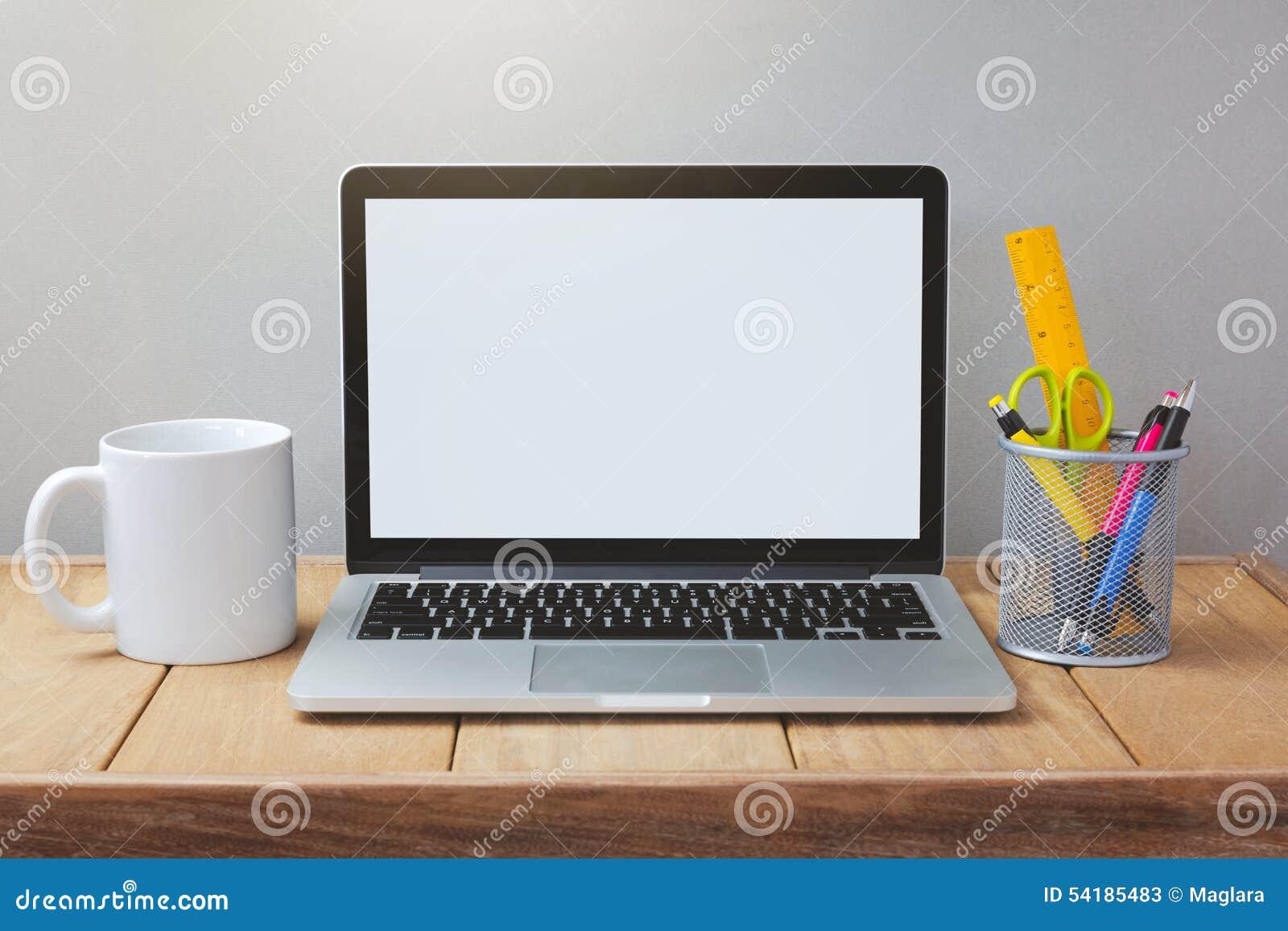 Ordenador portátil con la mofa blanca de la pantalla encima de la plantilla Escritorio de oficina con el ordenador; taza y pluma