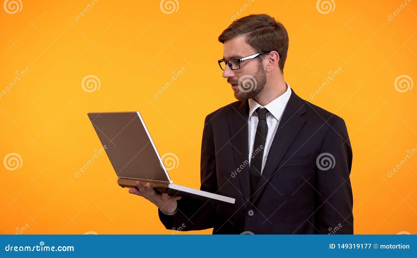 Ordenador port?til de la tenencia del hombre de negocios a disposici?n, leyendo el correo electr?nico, comprobando el nuevo traba