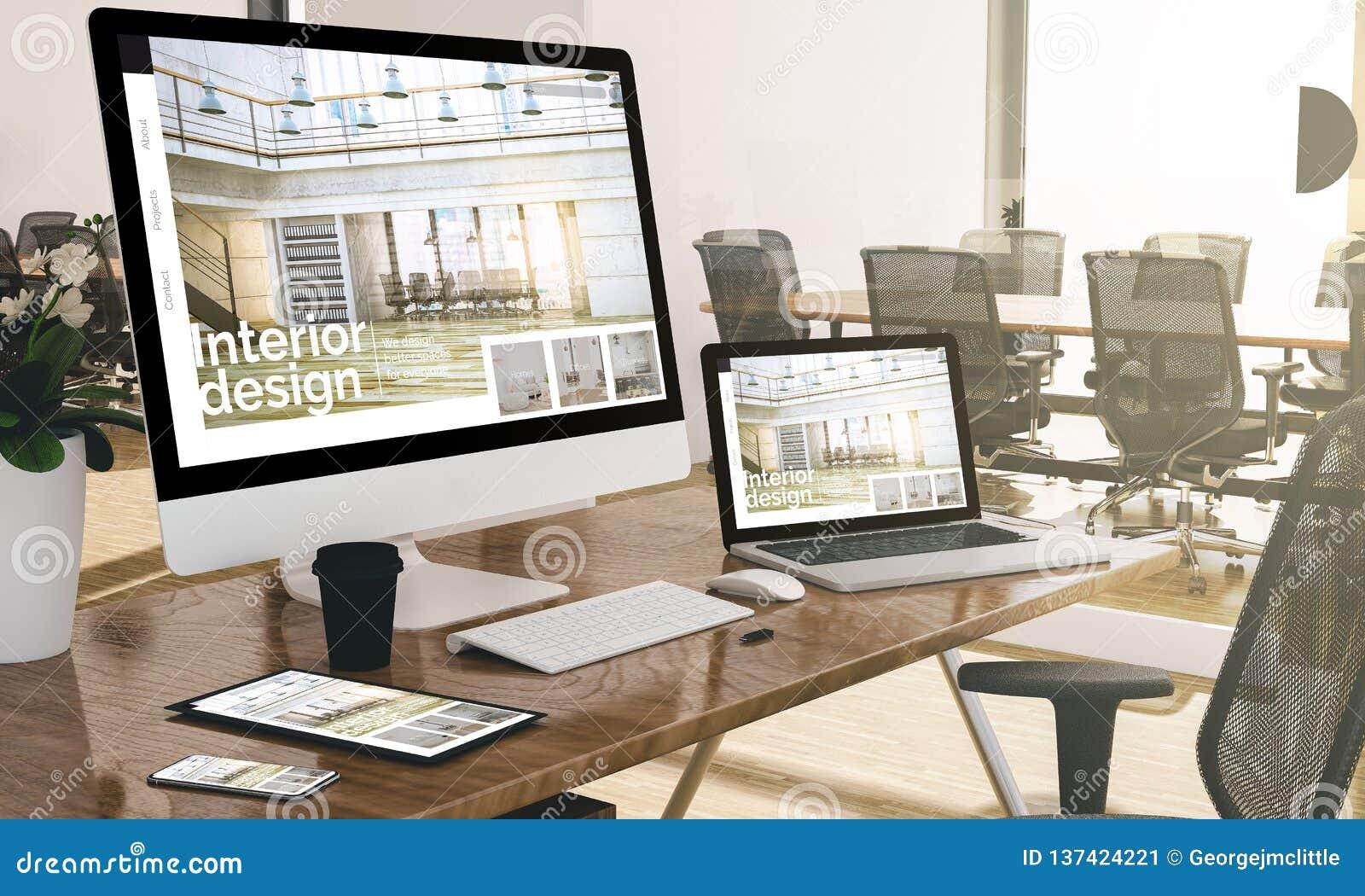 Ordenador, ordenador portátil, tableta, y teléfono con página web del diseño interior en la maqueta de la oficina
