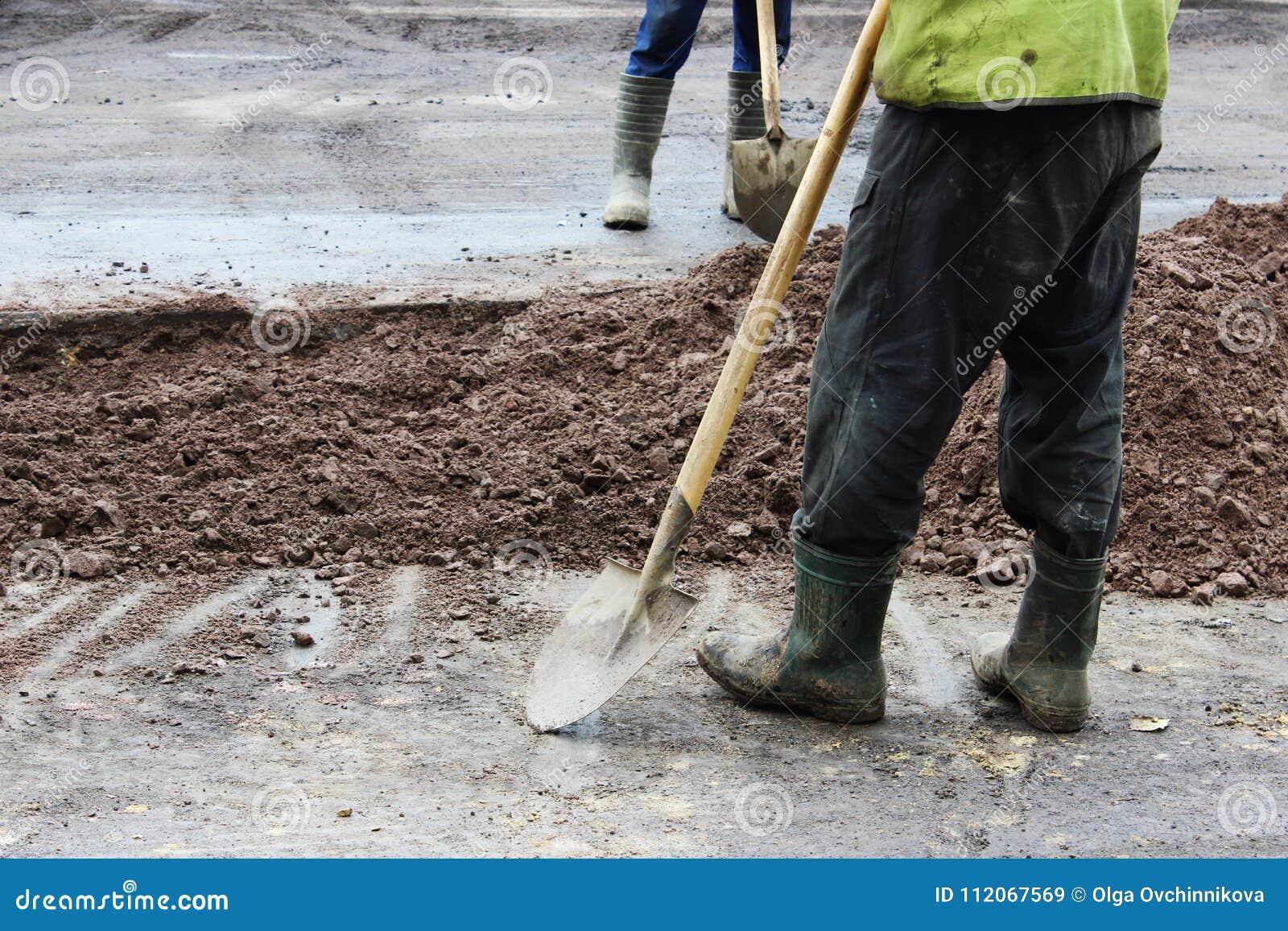 Ordföranden av byggmästare och en arbetare med en skyffel står nära problemområdet av vägen för arbete på utdragning av jord, des