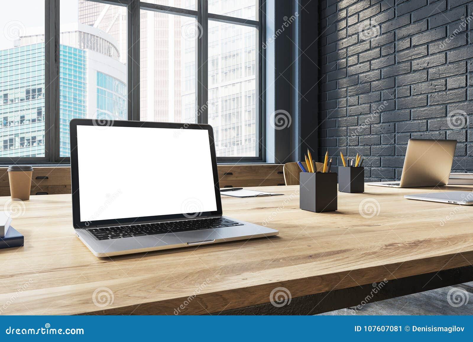 Ordinateur portable blanc d écran dans un bureau noir de brique
