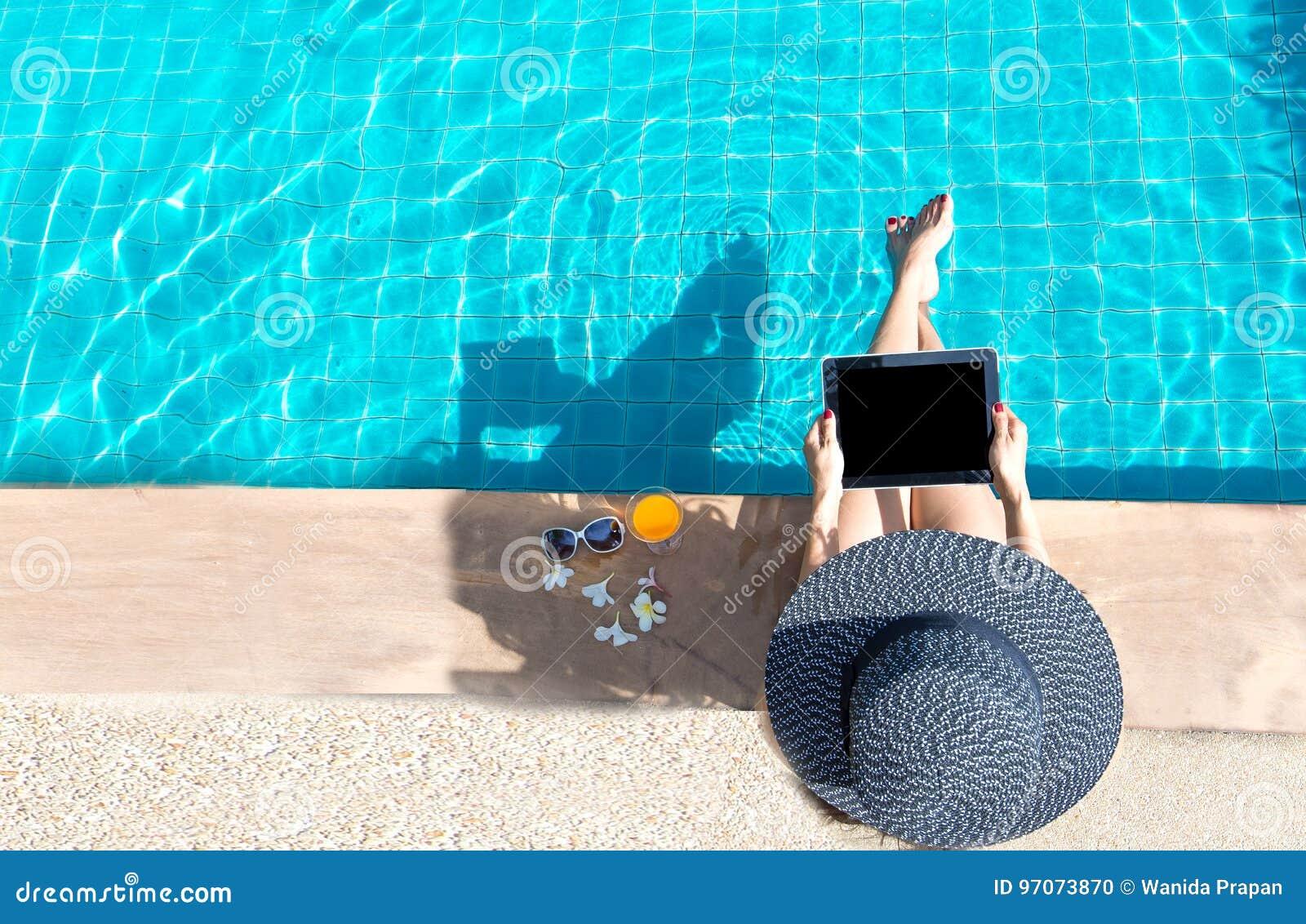 Ordinateur portable de jeu de mode de vie de femmes détendant près du bain de soleil de luxe de piscine, jour d été à la station