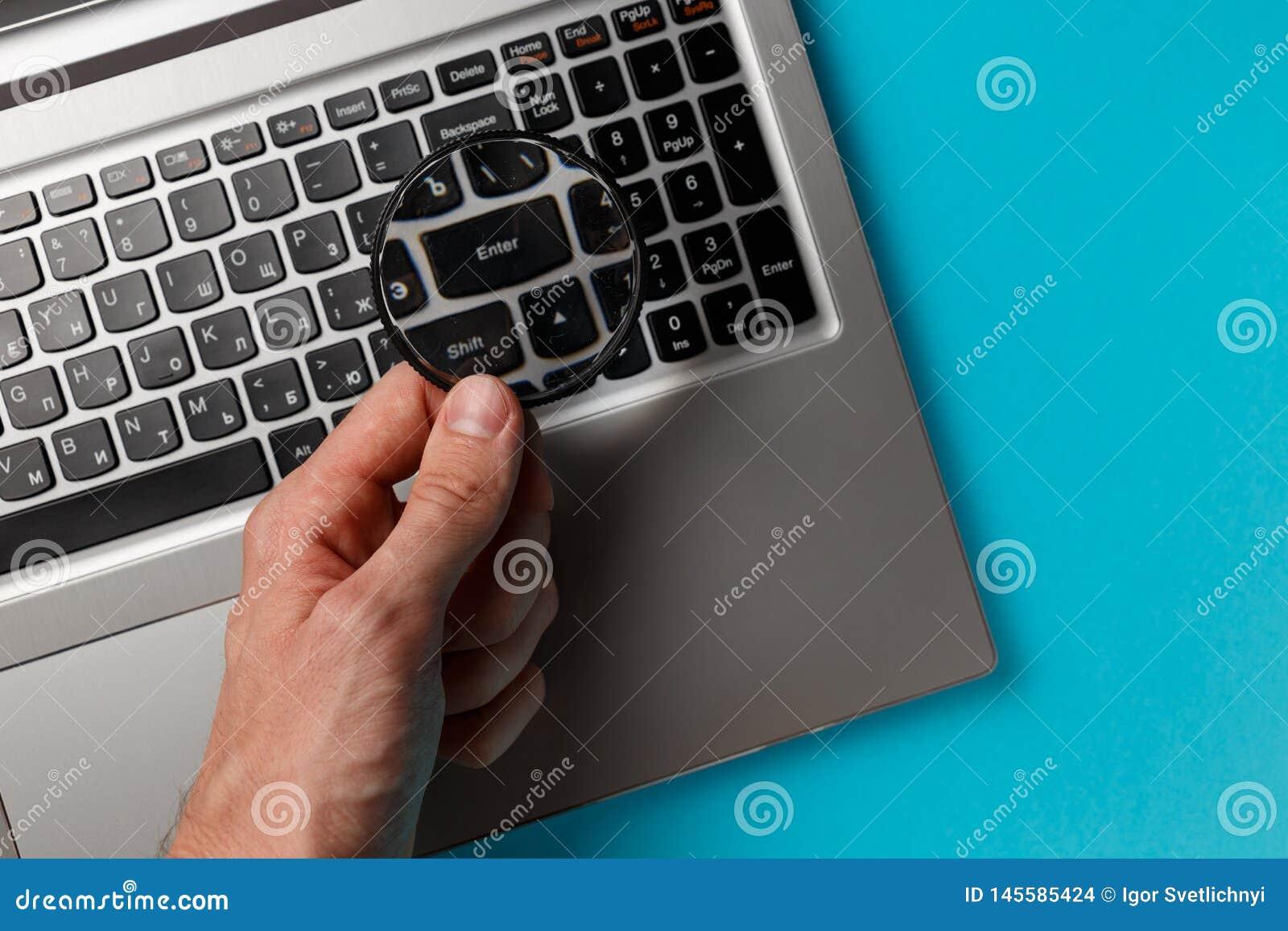 Ordinateur portable et main de l homme avec la loupe