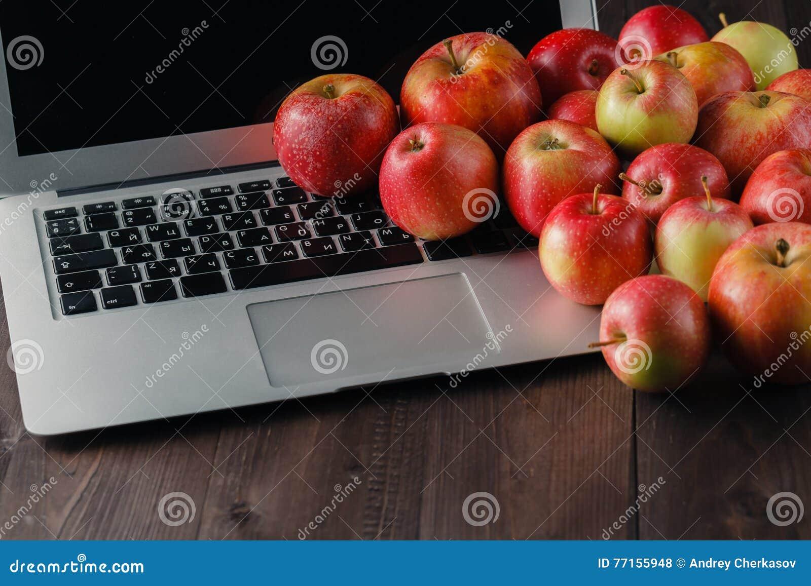 Ordinateur portable et pommes sur une table