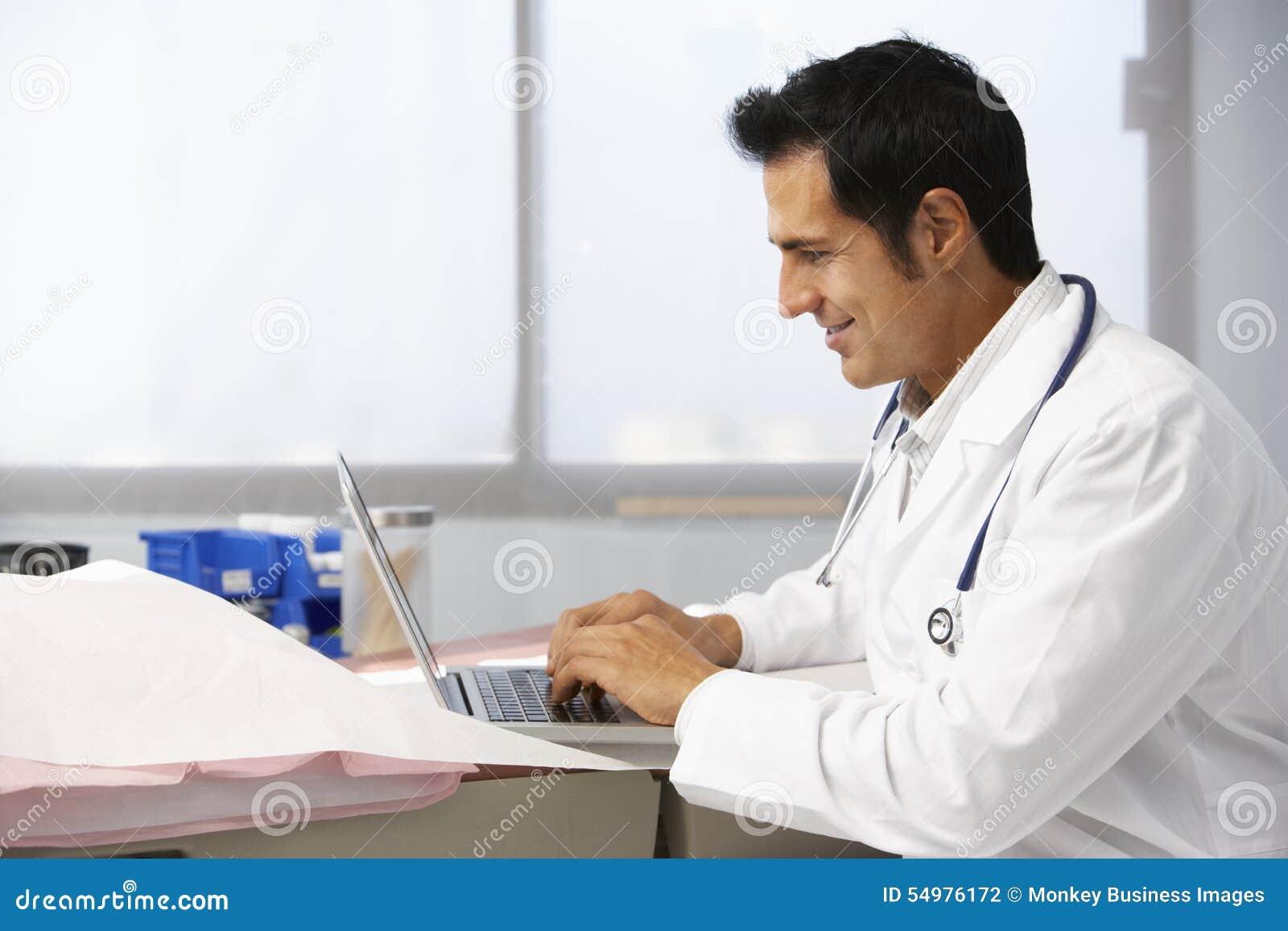 Ordinateur portable masculin de docteur In Surgery Using