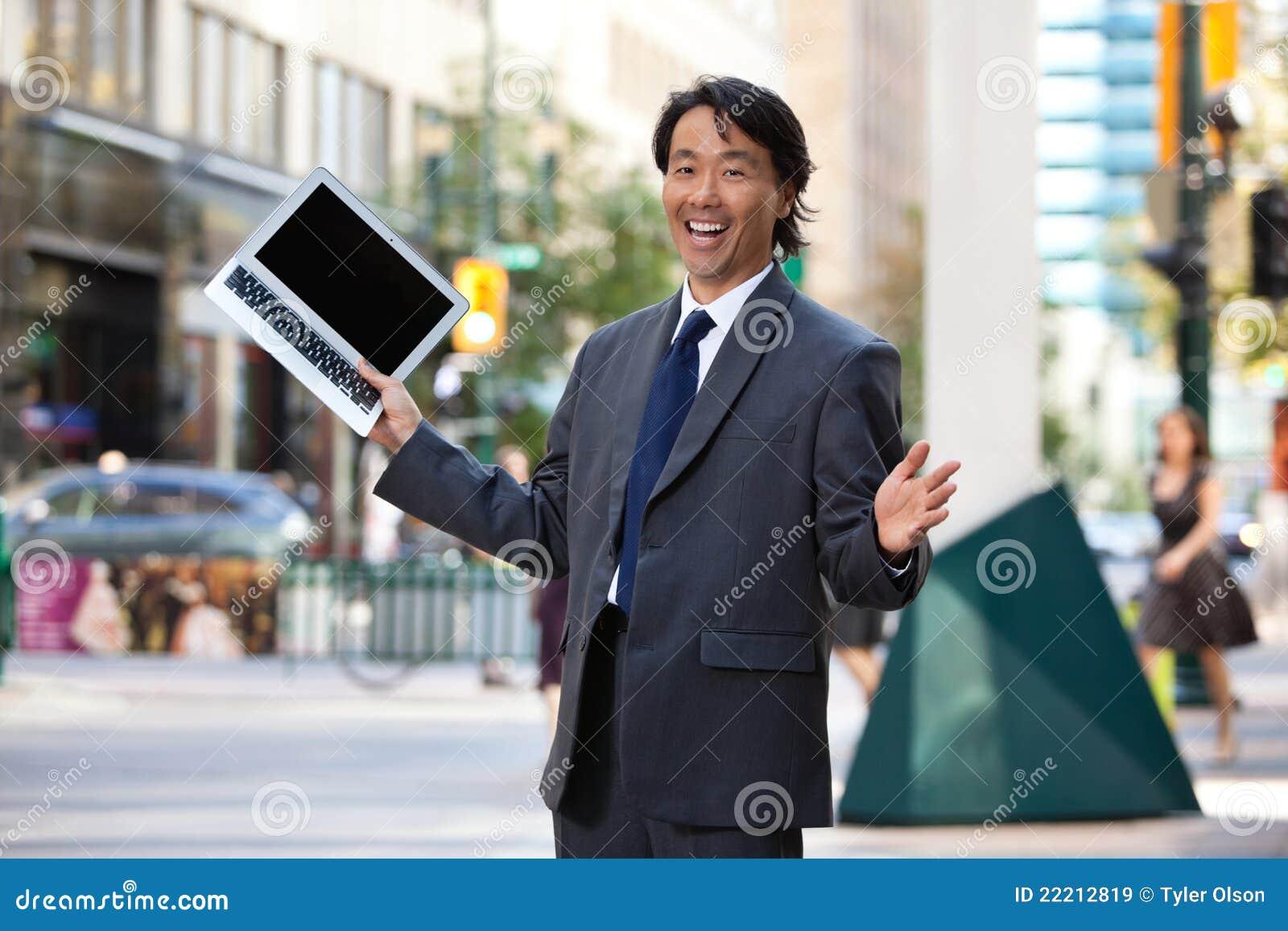 Ordinateur portatif et rire de fixation d homme d affaires