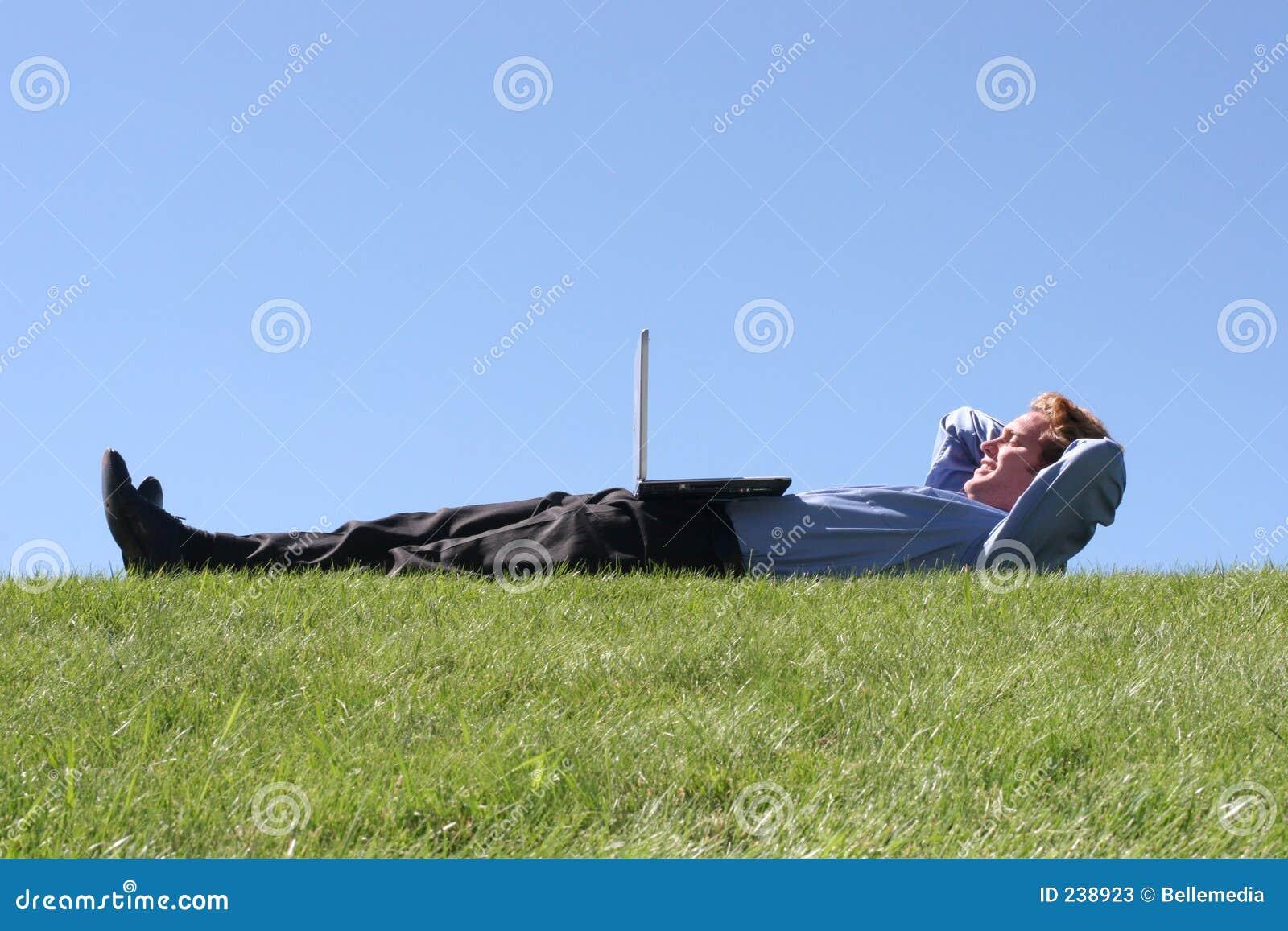 Ordinateur portatif sur l homme d affaires sur l herbe