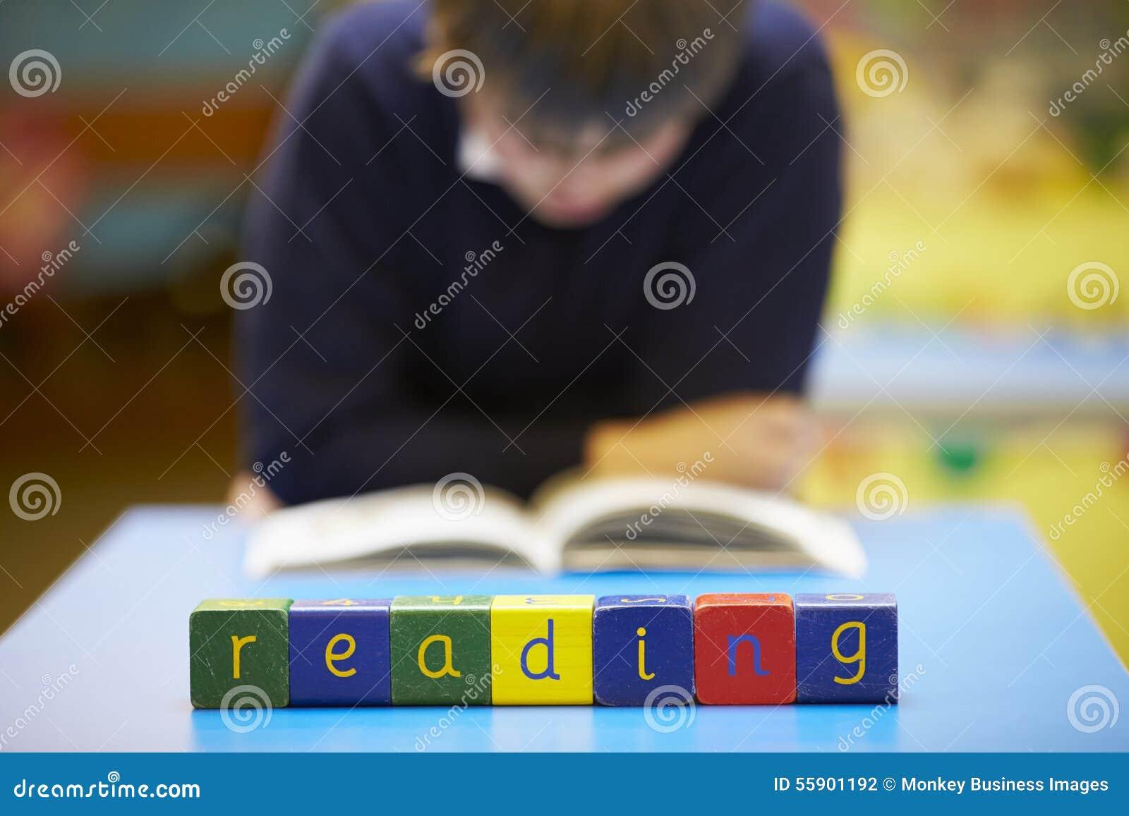 Ordläsning som stavas i träkvarter med eleven bakom