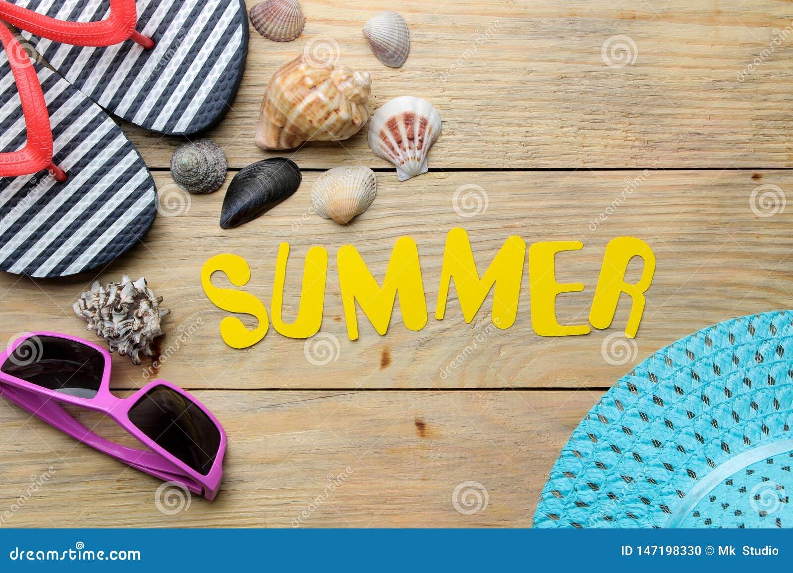 Ordsommaren som göras av pappers- gula bokstäver, och sommar, strandtillbehör på en naturlig träbakgrund Sommar semester relax