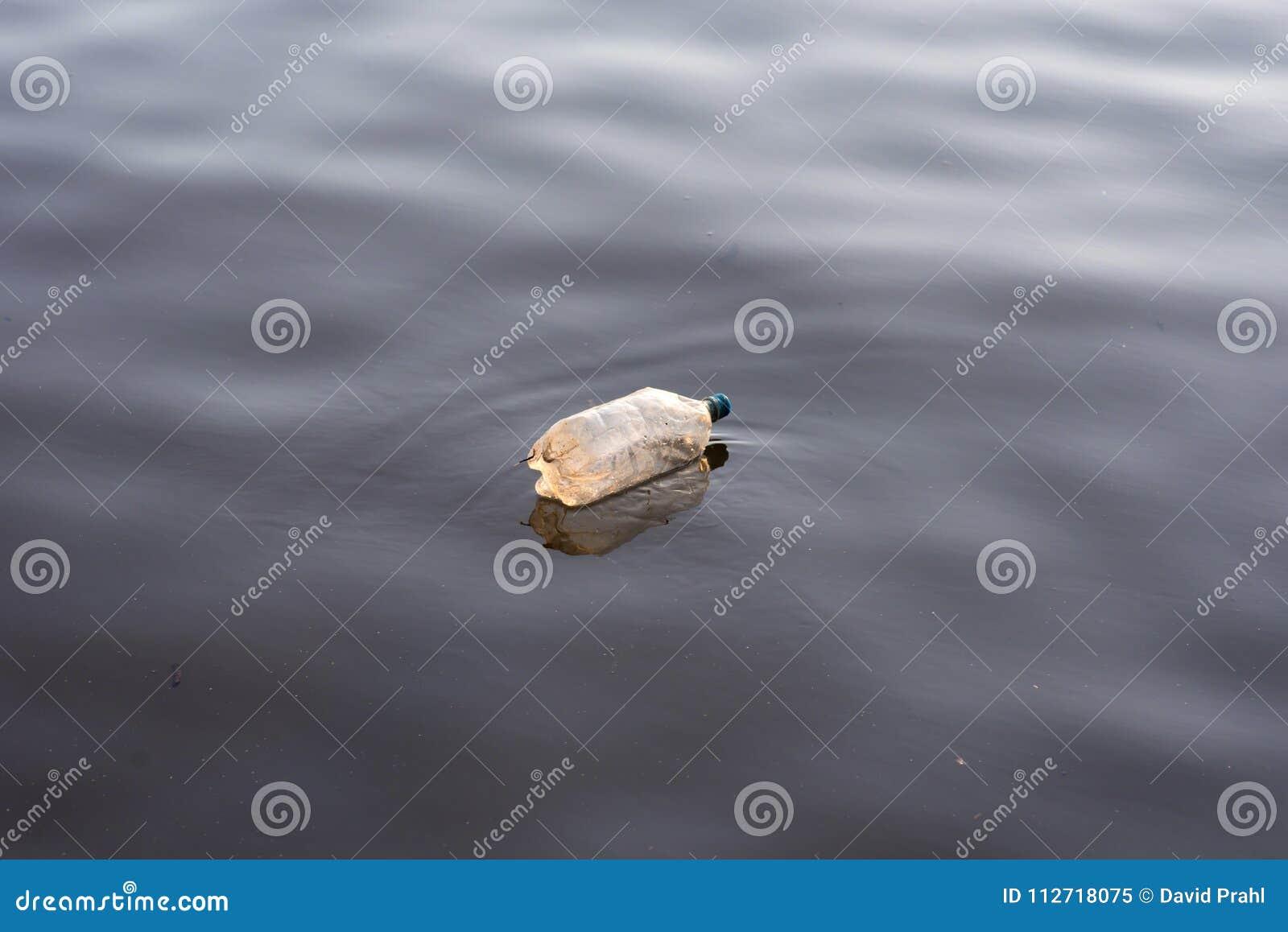 Ordures en plastique simples de bouteille d eau flottant dans l eau de lac