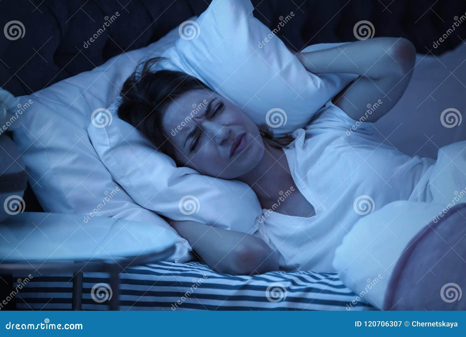 Orecchie della copertura della giovane donna con il cuscino mentre provando a dormire a letto