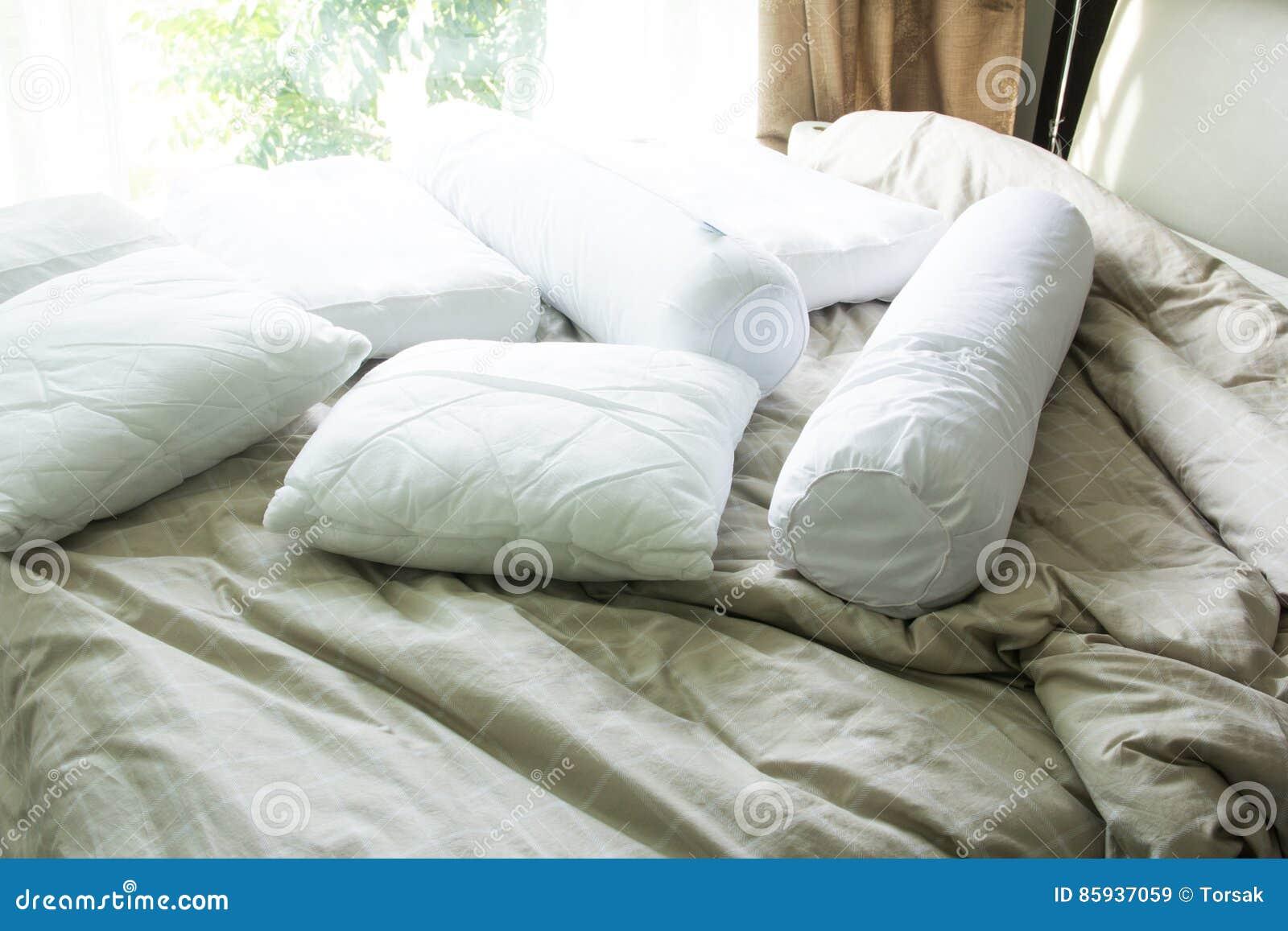 Oreiller avec le traversin sur le lit