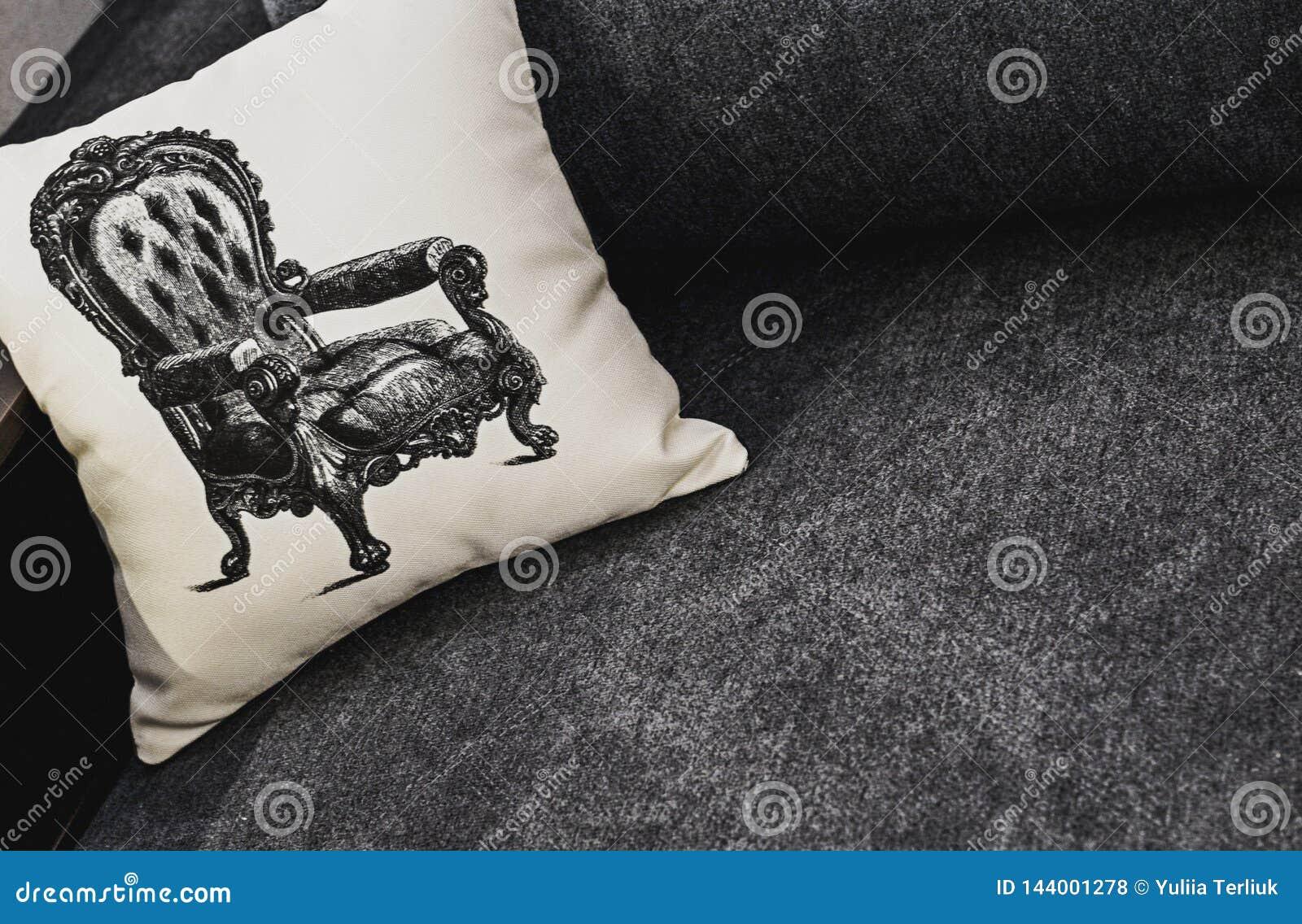 Oreiller blanc avec le modèle sur le sofa gris Repos, dormant, concept de confort Oreiller blanc avec le modèle de fauteuil