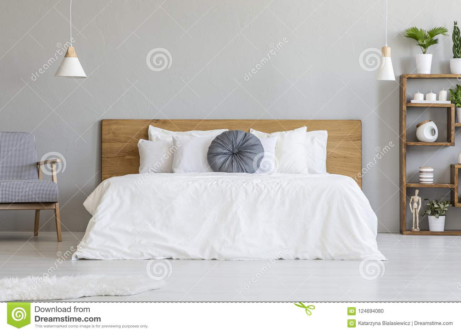 Oreiller bleu sur le lit blanc avec la tête de lit en bois dans l interi de chambre à coucher