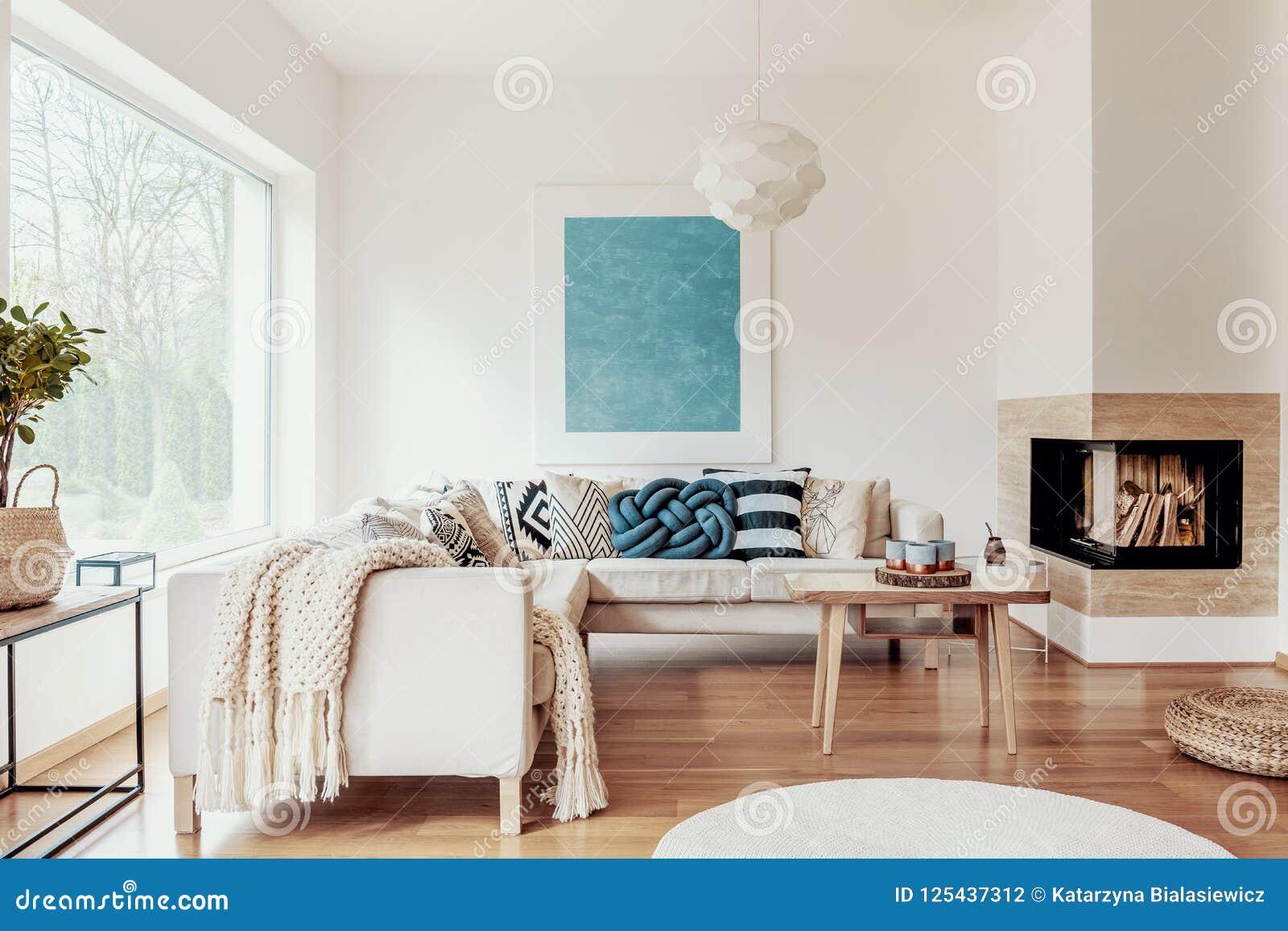 Oreiller de noeud de bleu de turquoise sur un sofa faisant le coin beige et une affiche abstraite sur un mur blanc dans un intéri