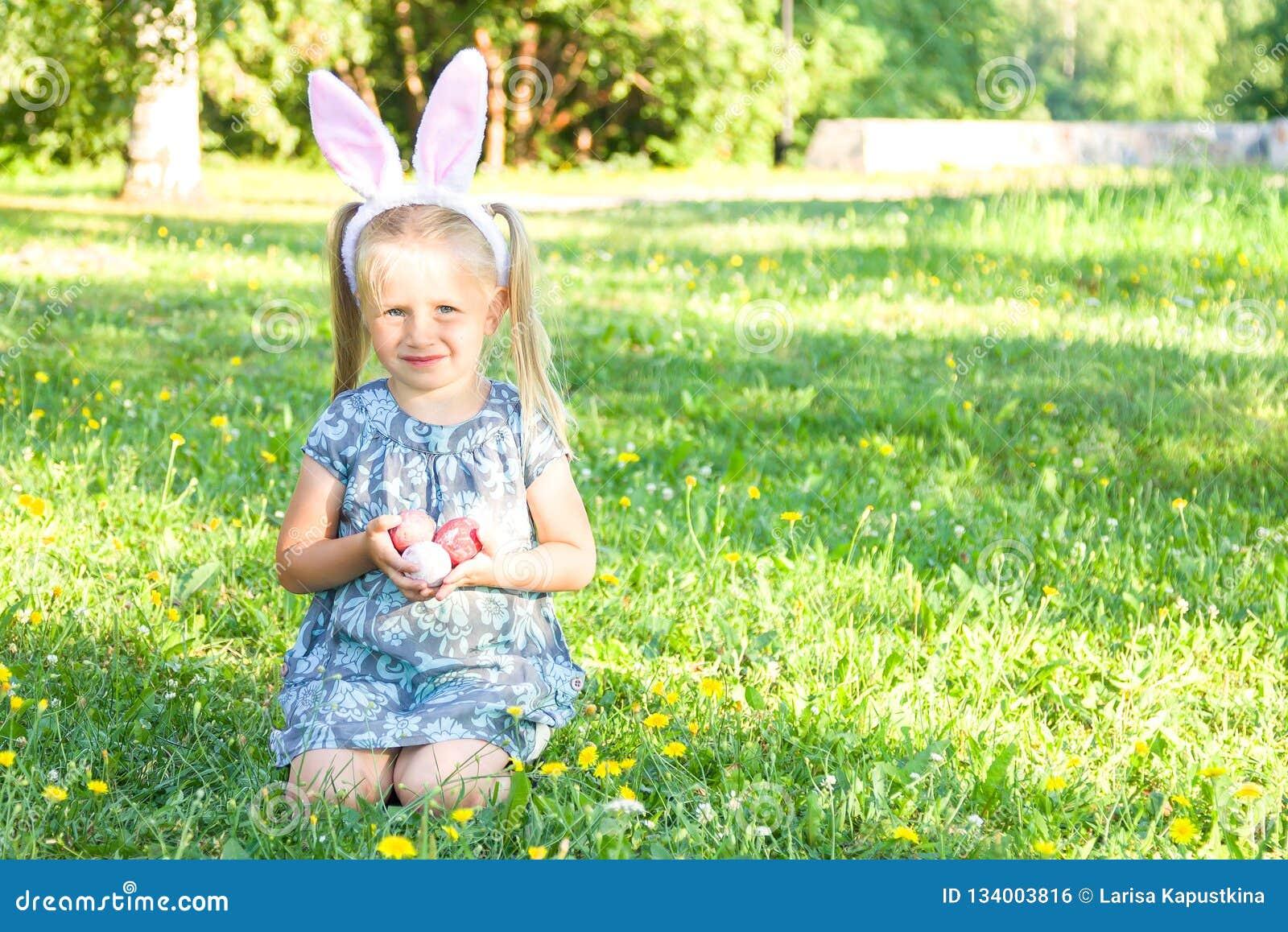 Oreilles de port mignonnes de lapin de petite fille le jour de Pâques Fille s asseyant sur une herbe et tenant les oeufs de pâque