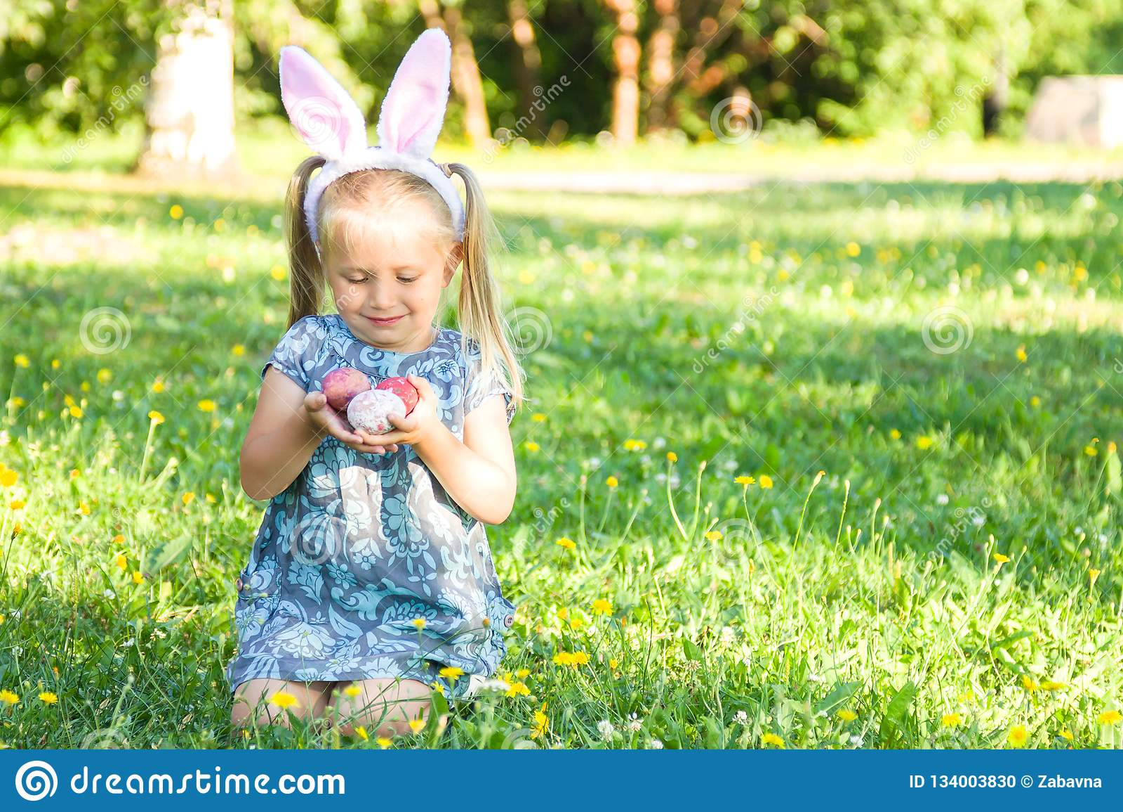 Oreilles de port de sourire mignonnes de lapin de petite fille le jour de Pâques Fille s asseyant sur une herbe et tenant les oeu