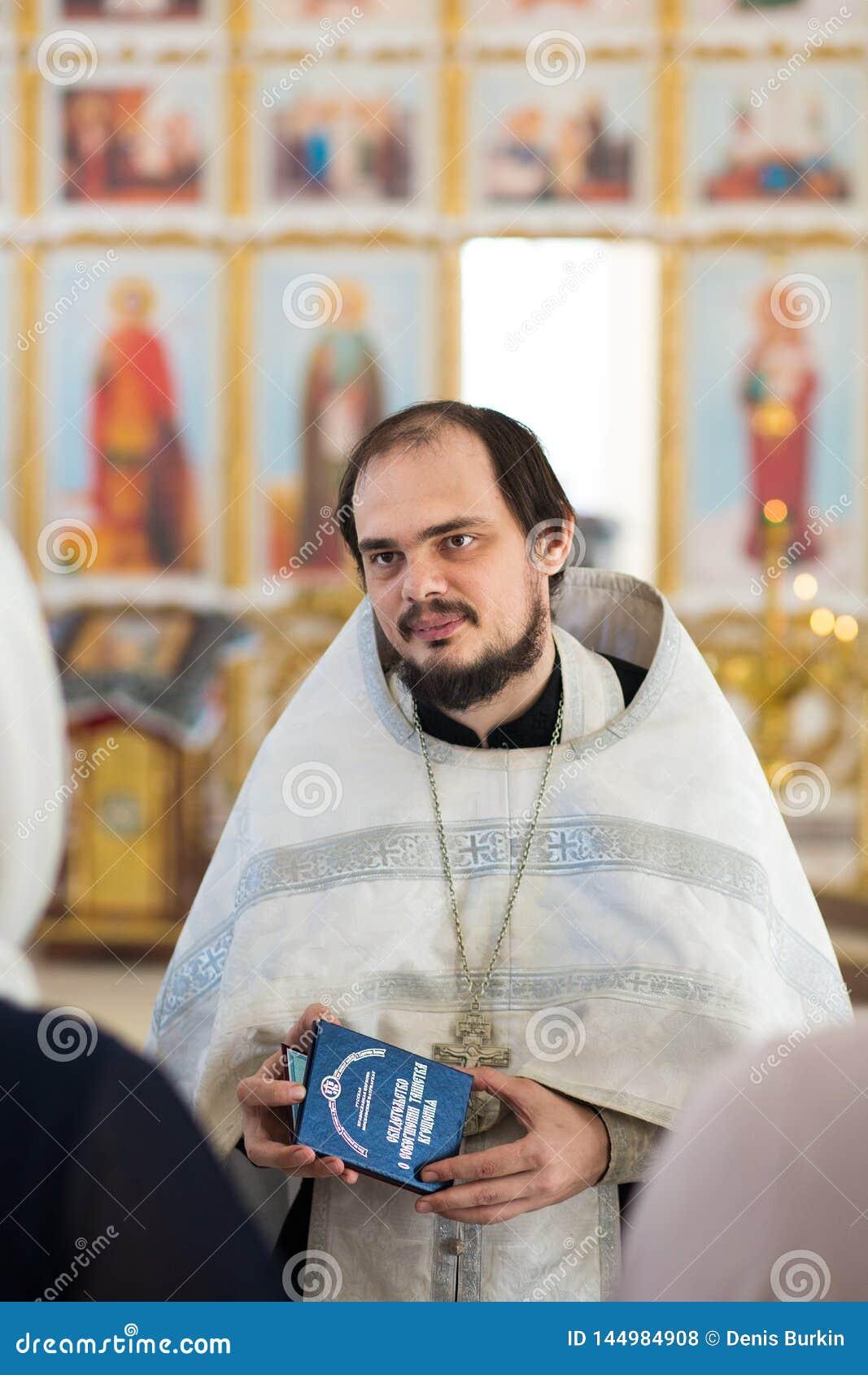 Orenburg, Federation-2 ruso Aprel 2019 Un sacerdote ortodoxo joven sostiene un certificado de bautismo en sus manos