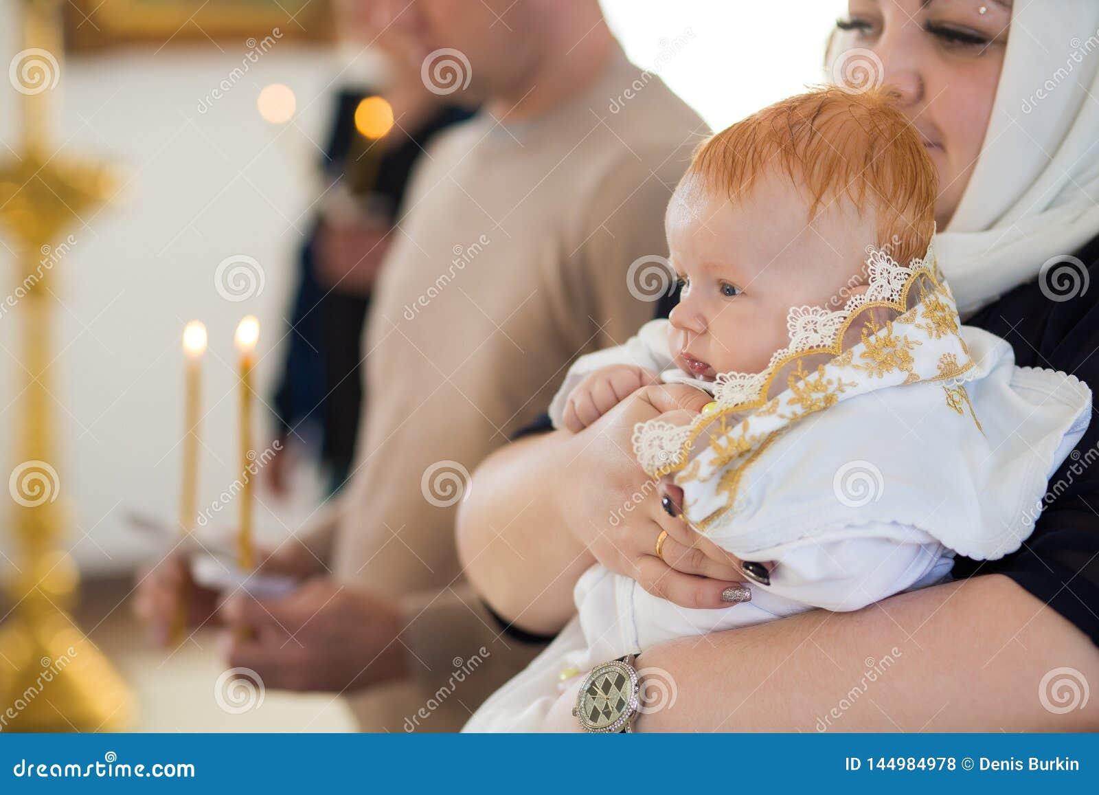 Orenburg, rosjanin Federation-2 Aprel 2019 Kobieta trzyma dziecka podczas ochrzczenie rytuału