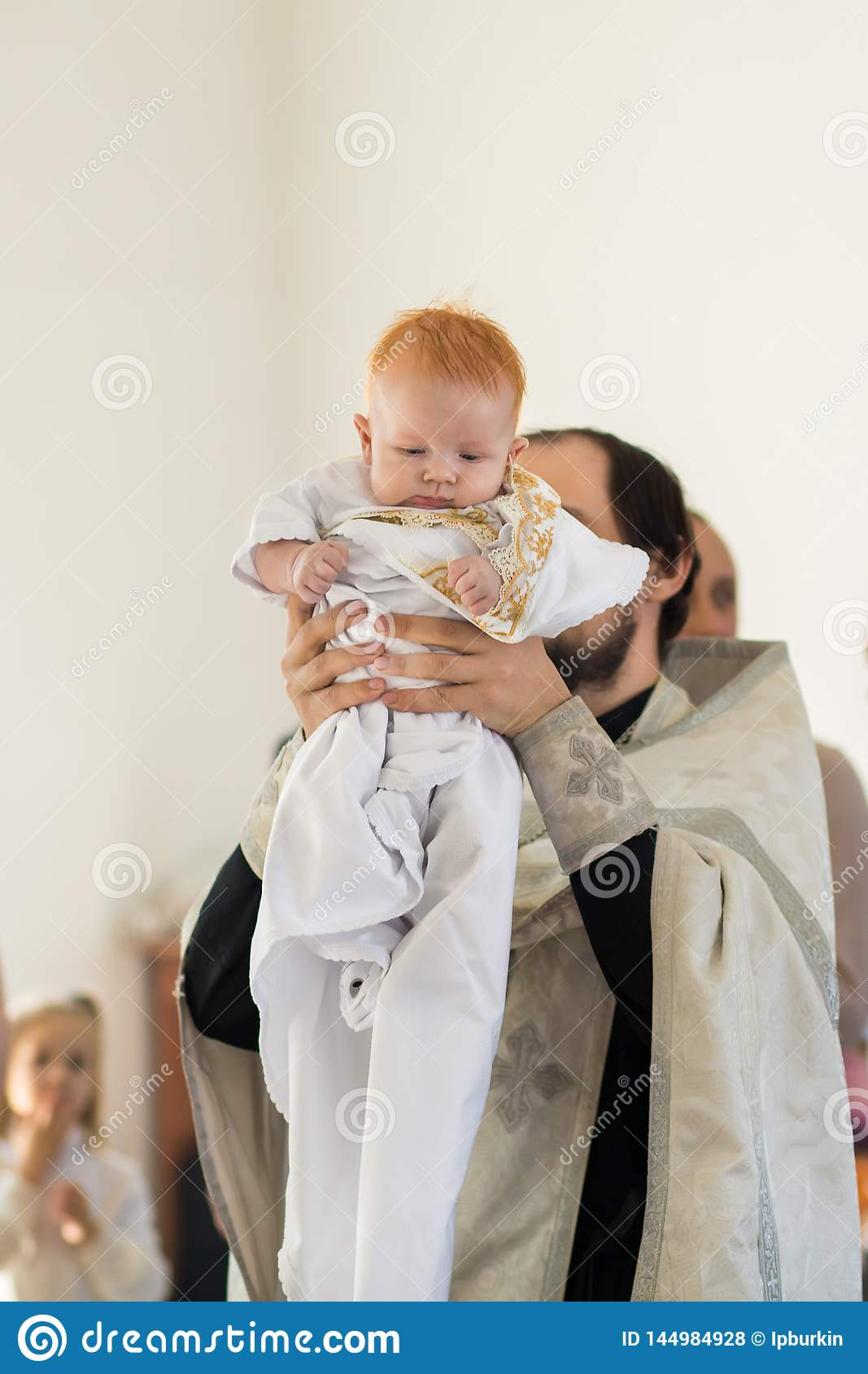 Orenburg, Russian Federation-2 Aprel 2019. Orthodox priest holding a baby during the baptism ritual