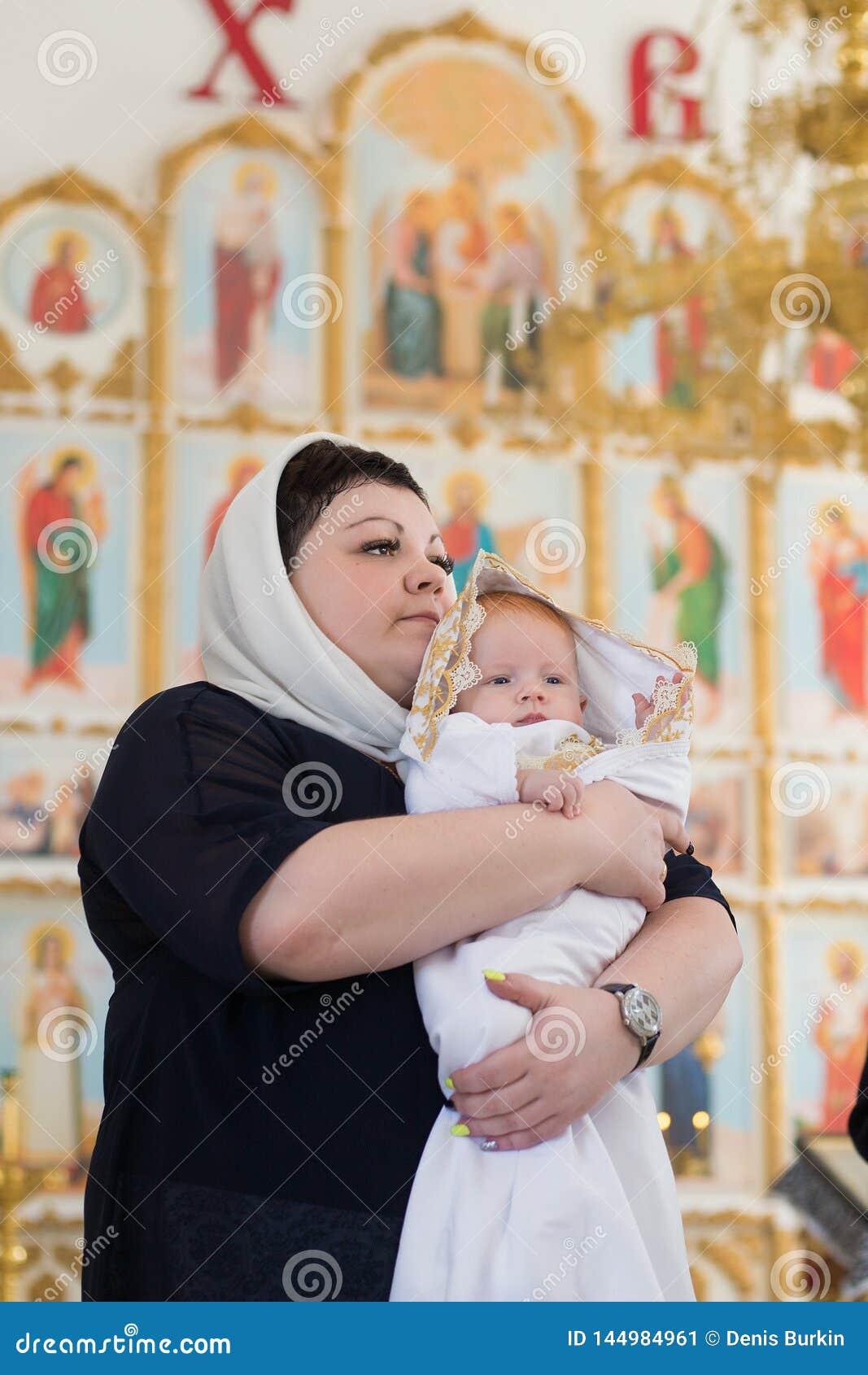 Orenburg, russisches Federation-2 Aprel 2019 Frau, die ein Baby während des Tauferituals hält
